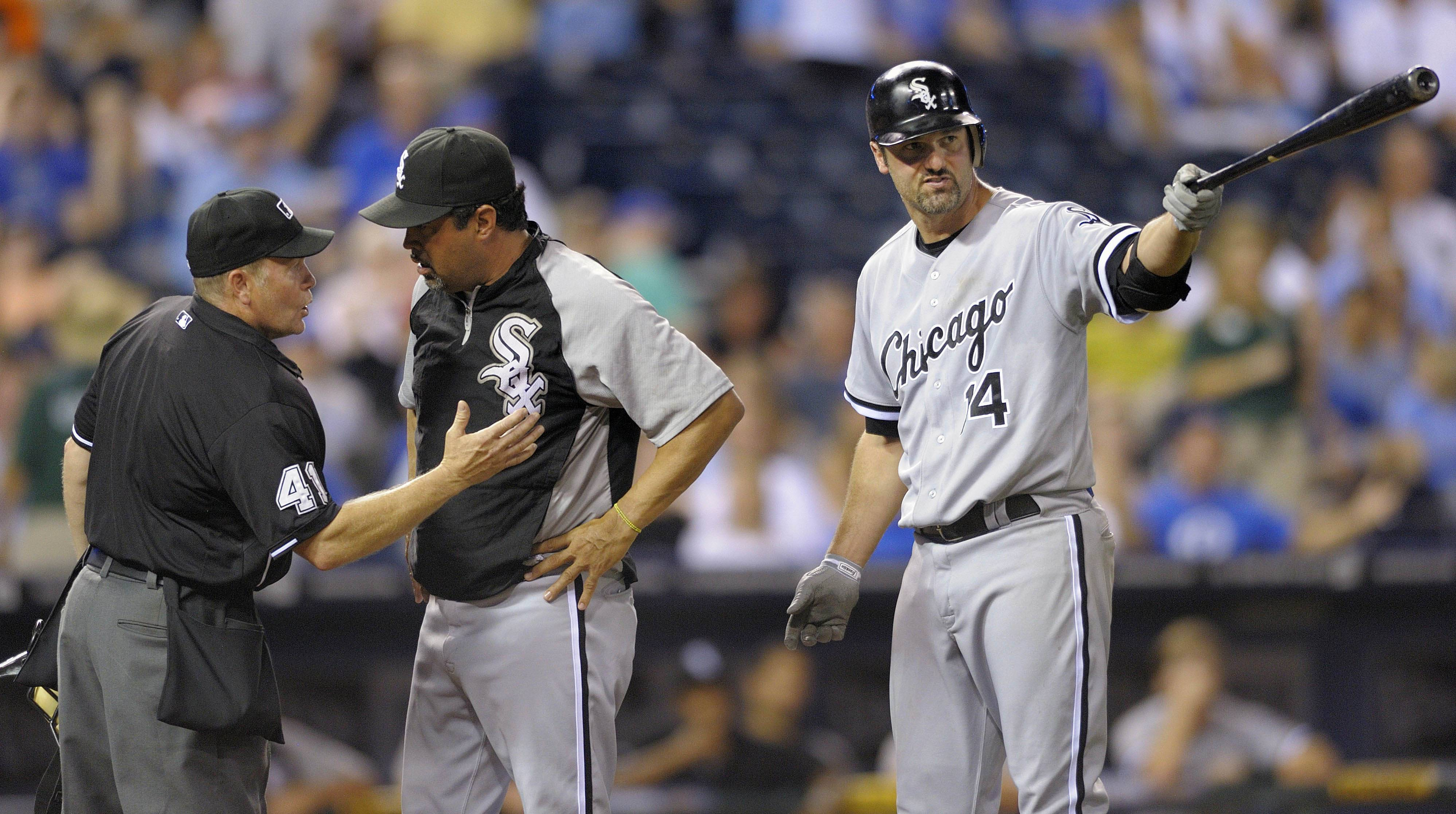Ozzie Guillen, center, argues a call against Chicago White Sox first baseman Paul Konerko (14) with home plate umpire Jerry Meals, left, in the ninth inning of their baseball game against the Kansas City Royals in Kansas City, Mo., Wednesday, July 20, 2011.