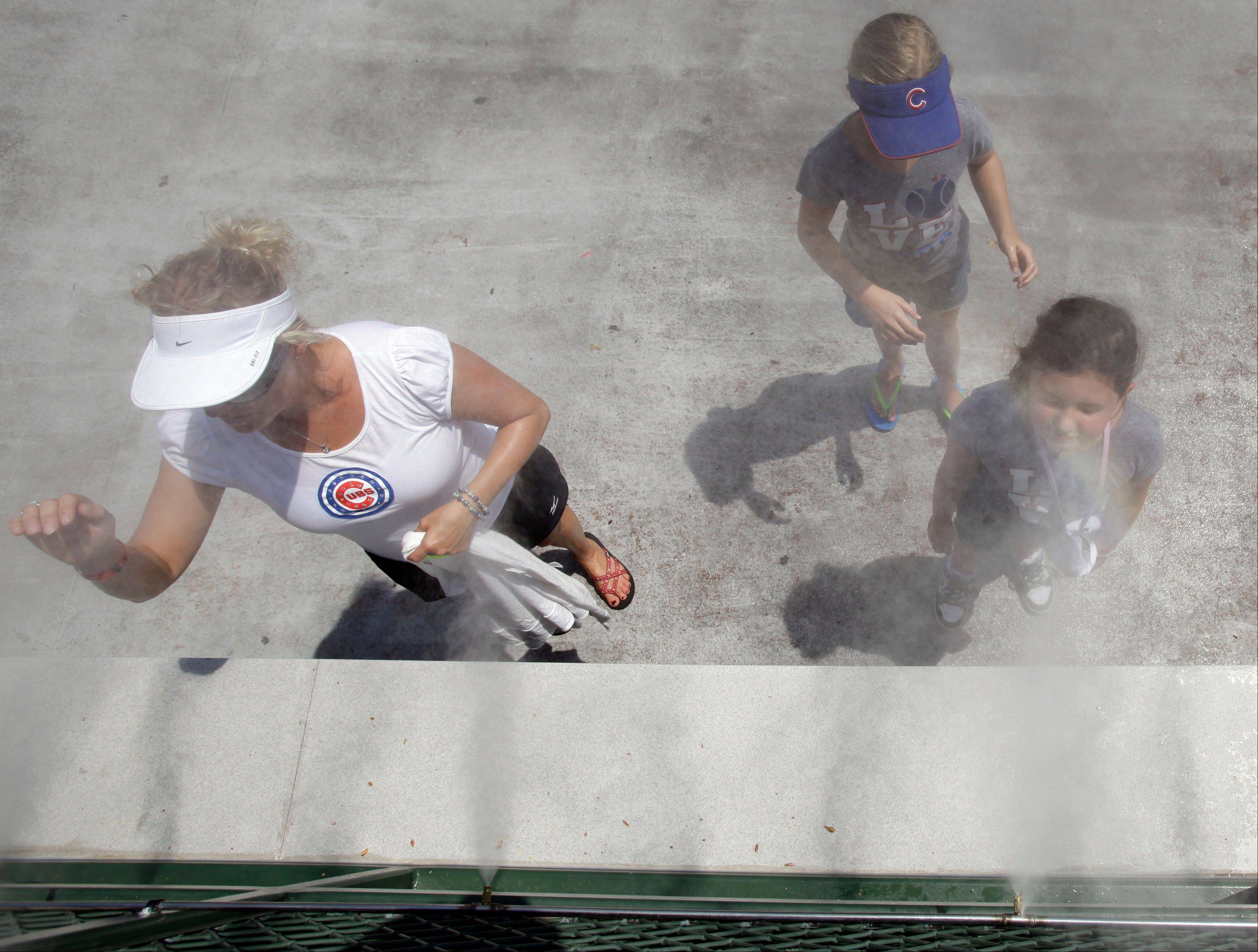 Baseball fans cool off in the mist before the Cubs' game Wednesday afternoon.