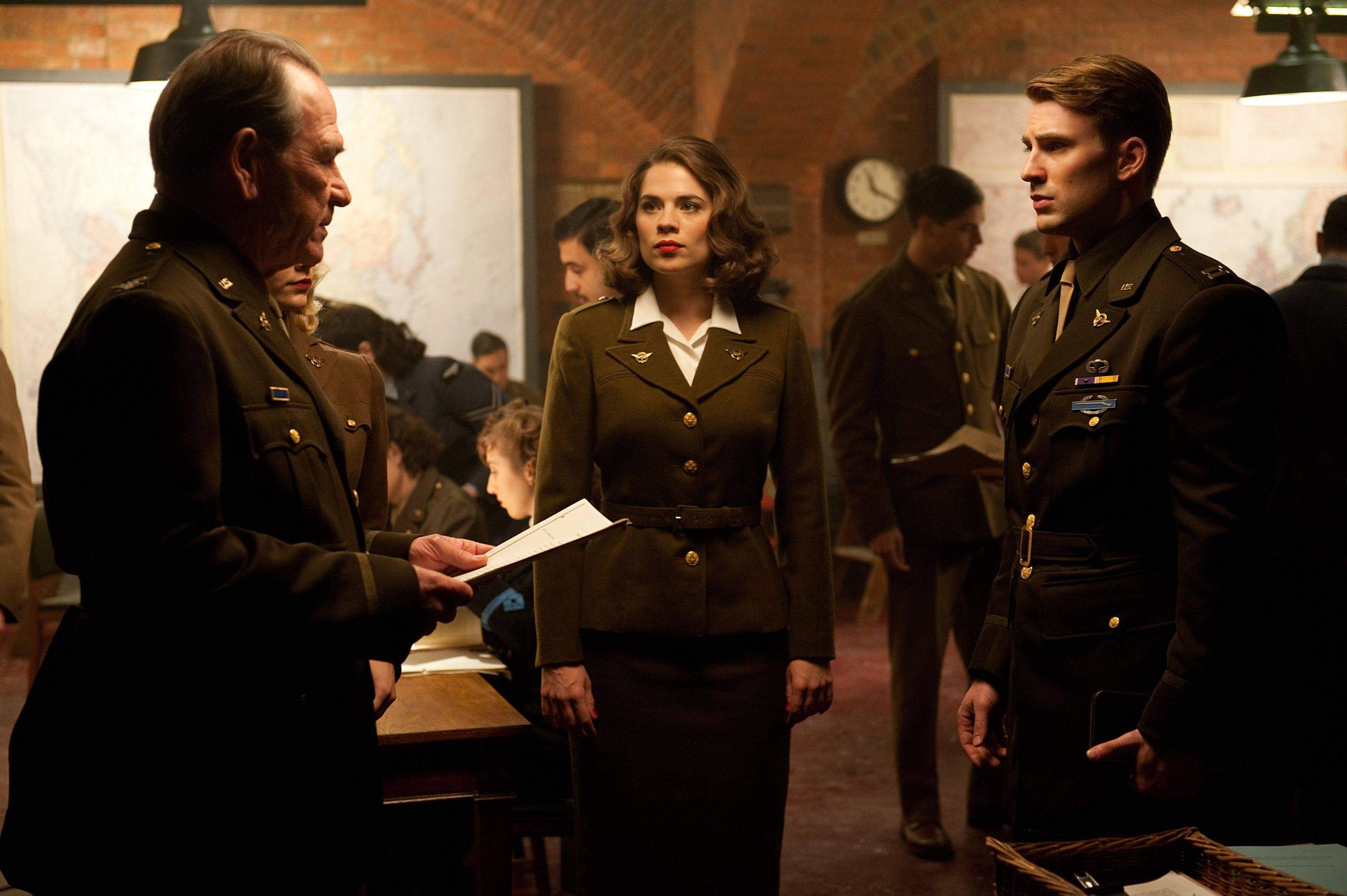 "Steve Rogers, aka Captain America (Chris Evans), right, discusses strategy with Col. Chester Phillips (Tommy Lee Jones) and Agent Peggy Carter (Hayley Atwell) in ""Captain America: The First Avenger."""