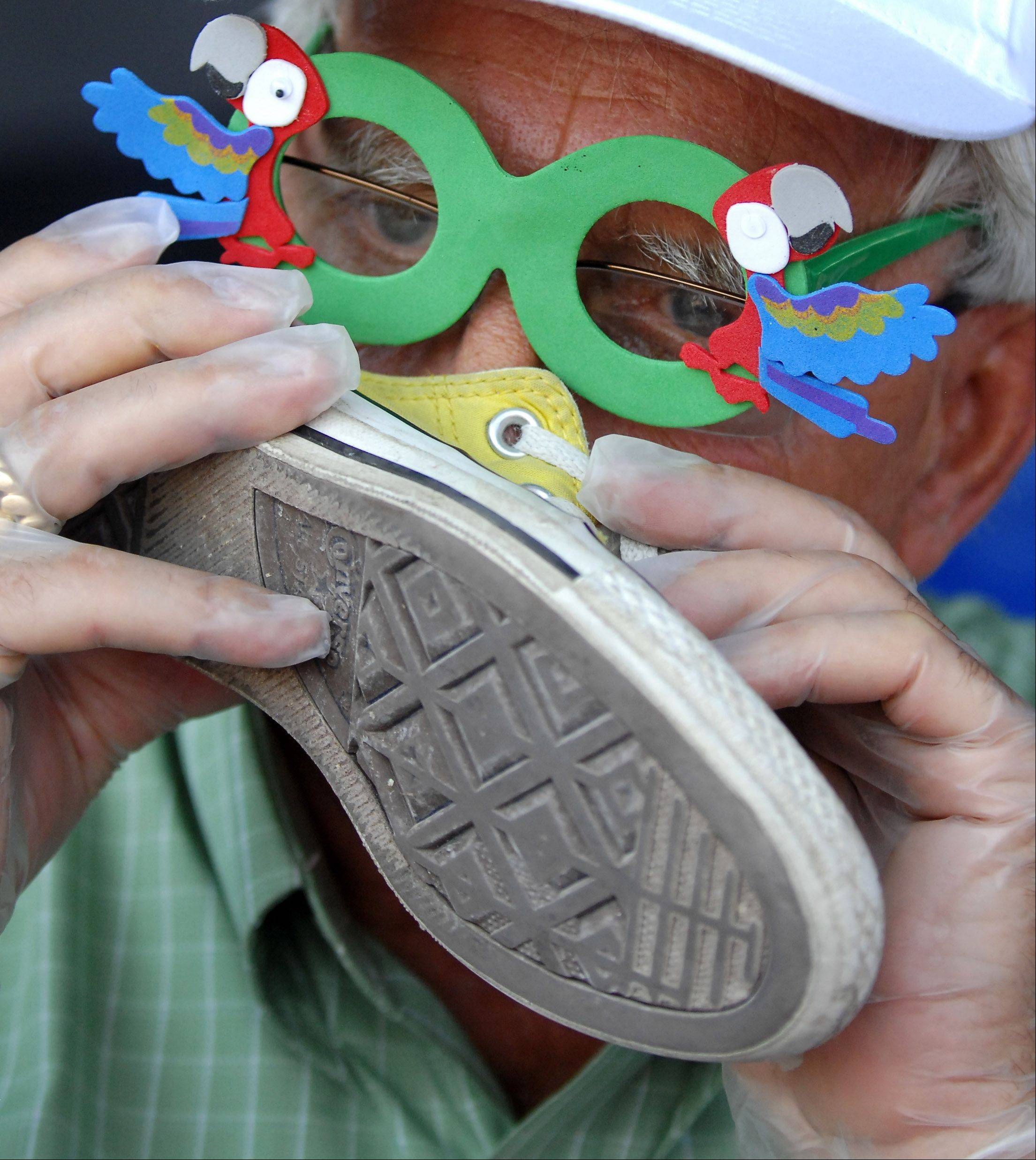 Judge Gene Schick sticks his nose right in there while trying to pick a winner at the Odor Eaters Rotten Sneaker Contest at the Kane County Fair in St. Charles Thursday. Schick is a member of the fair board and lives in Elgin. The novelty glasses allegedly aided in odor detection.
