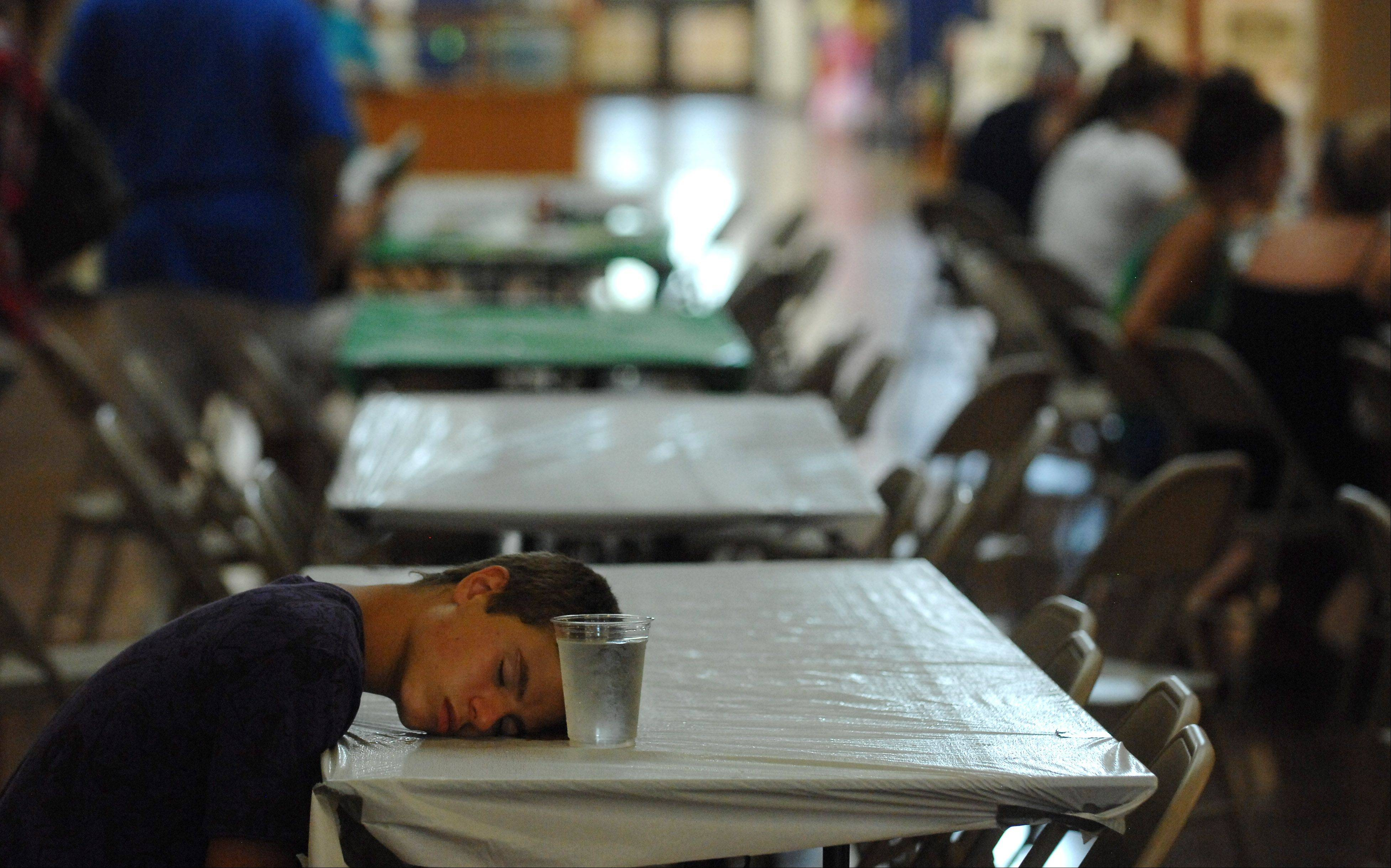 Dakota Purtell, 15, of Warrenville puts his head down in the air-conditioned hall during day two of the Kane County Fair in St. Charles Thursday. He said he had gone on a couple of rides but the heat made him sick, so he went in to rest his head on a damp napkin.