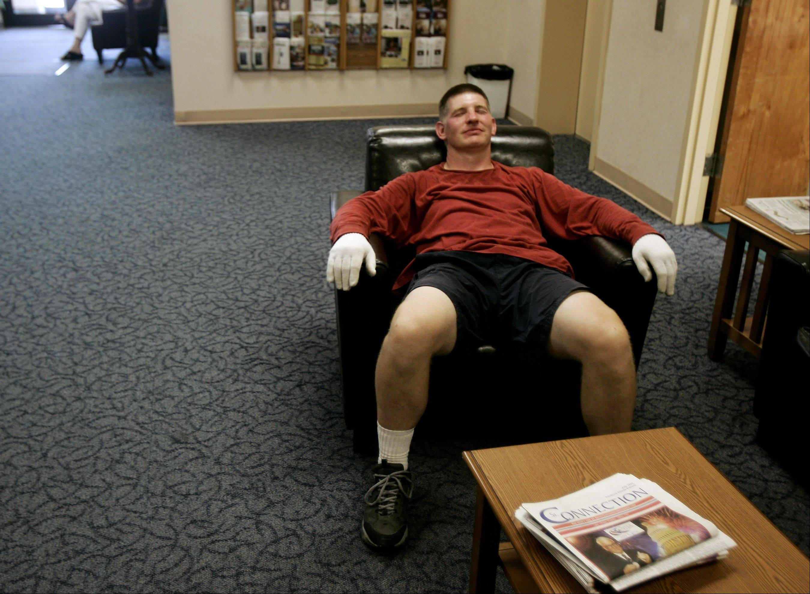 Greg Rosenquist of Staff of Life Farms collapses in a chair as he take a break in the cooling center Thursday at the Libertyville Civic Center.Rosenquist spent the morning making popcorn at the Libertyville Farmers Market.