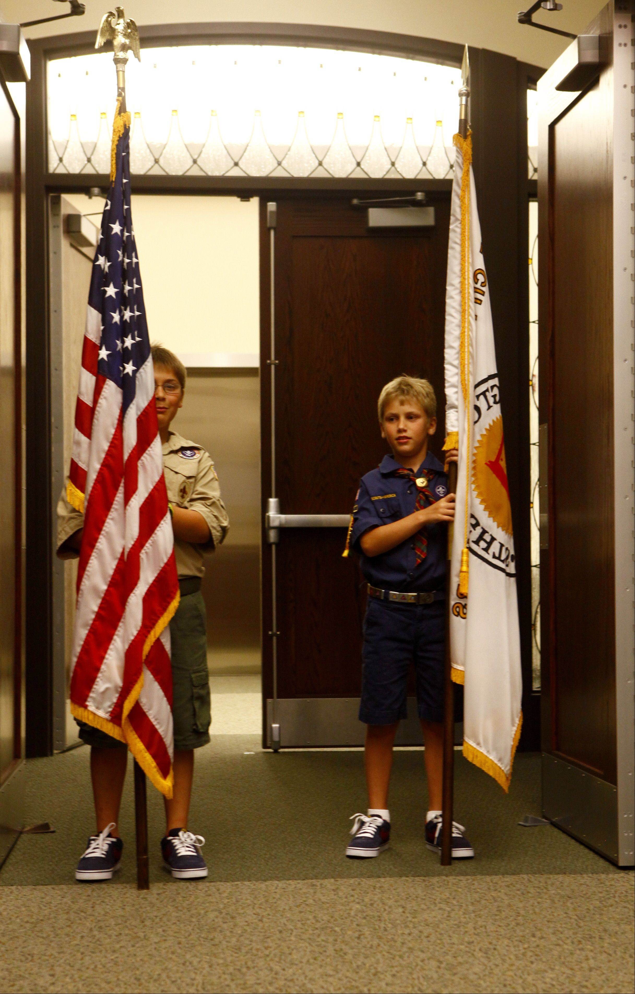 Rides Scerbin, left, and his brother, Max, carry the flags before the meeting of the Arlington Heights Village Board Monday, July 18.