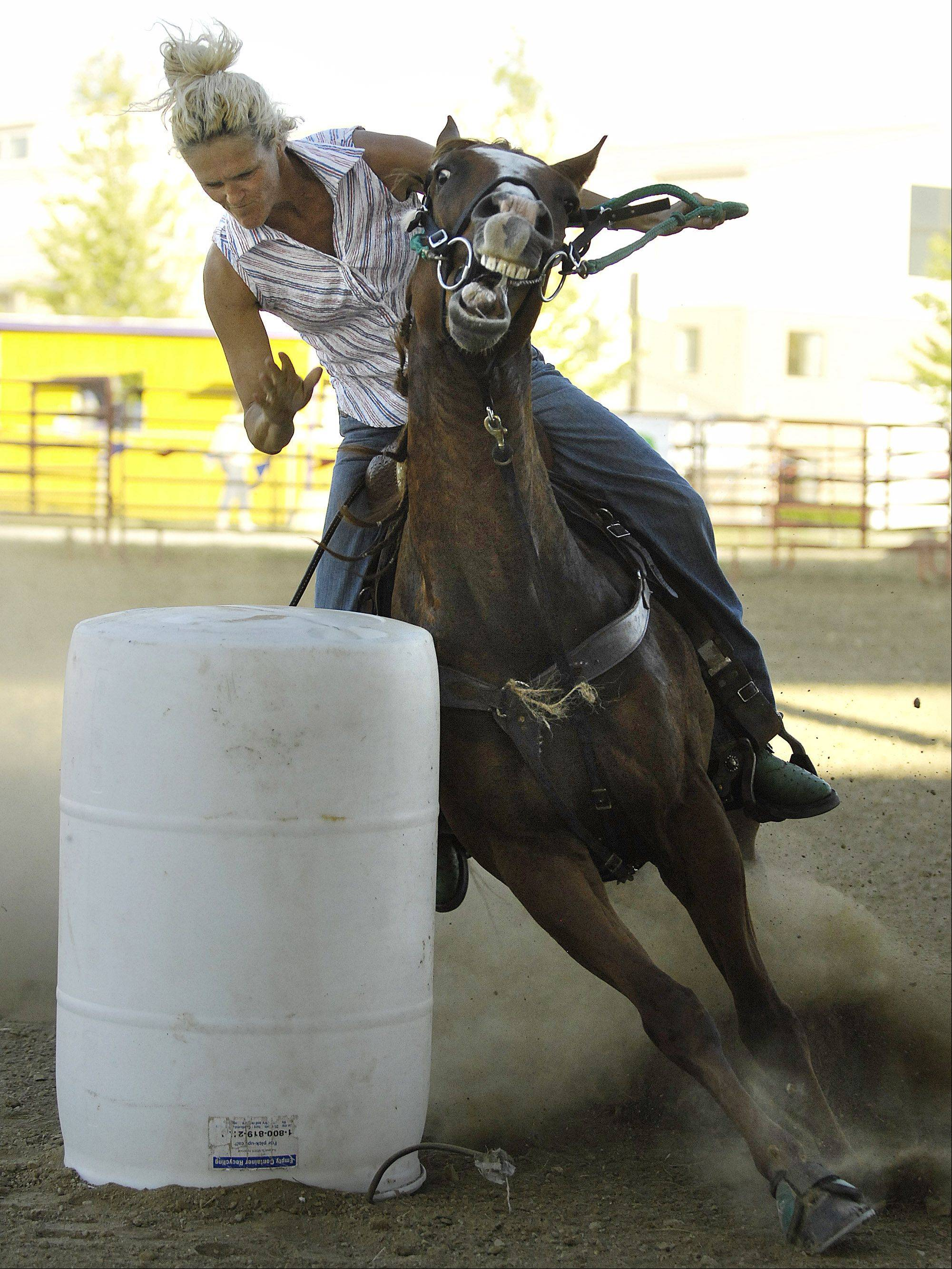 Charlene Whitaker reaches out to touch a barrel as her horse charges around it during barrel racing at the Kane County Fair Wednesday in St. Charles.