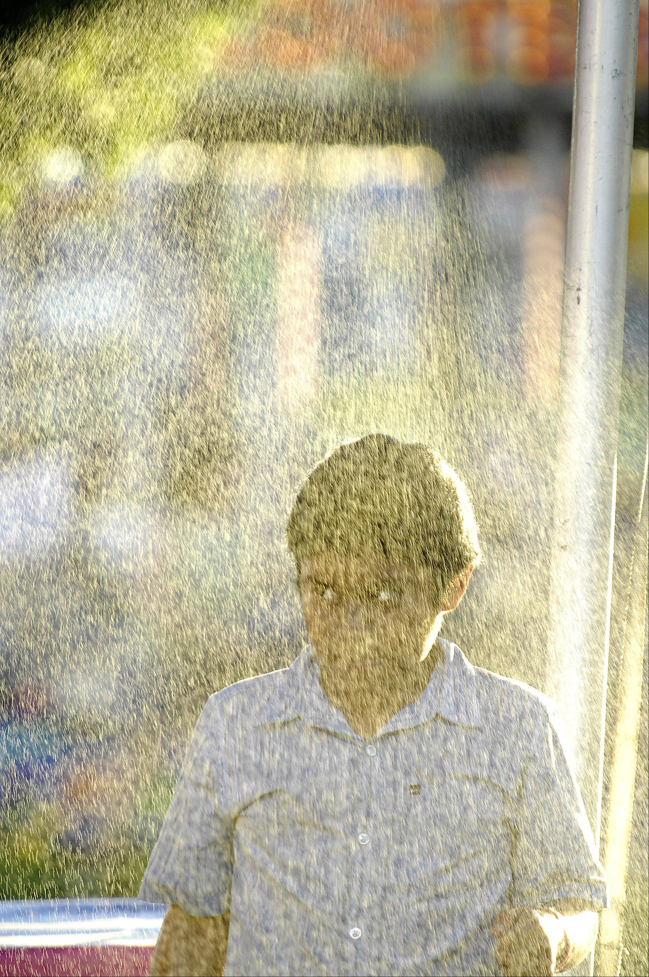 The setting sun makes a spray mist reflect colors as Daniel Olonso, 9, walks under it during the first day of the Kane County Fair Wednesday in St. Charles.
