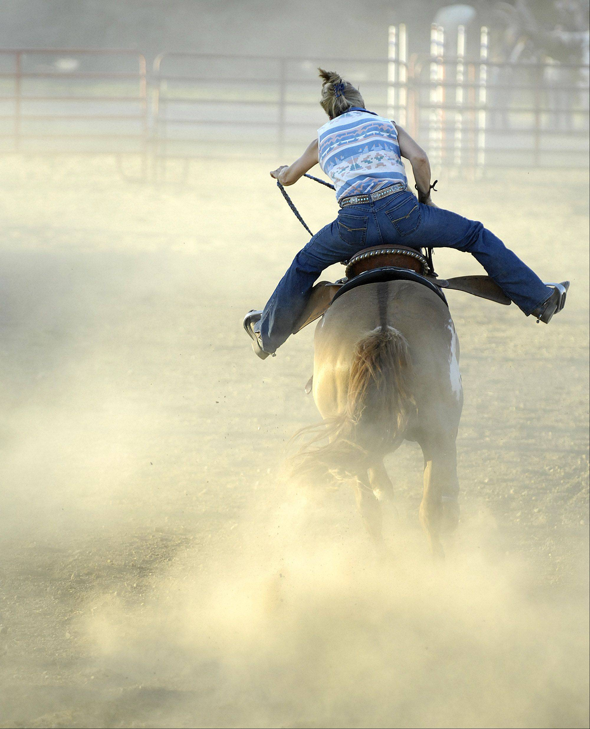 A rider finishes her barrel race run in a cloud of dust during the first day of the Kane County Fair Wednesday in St. Charles.