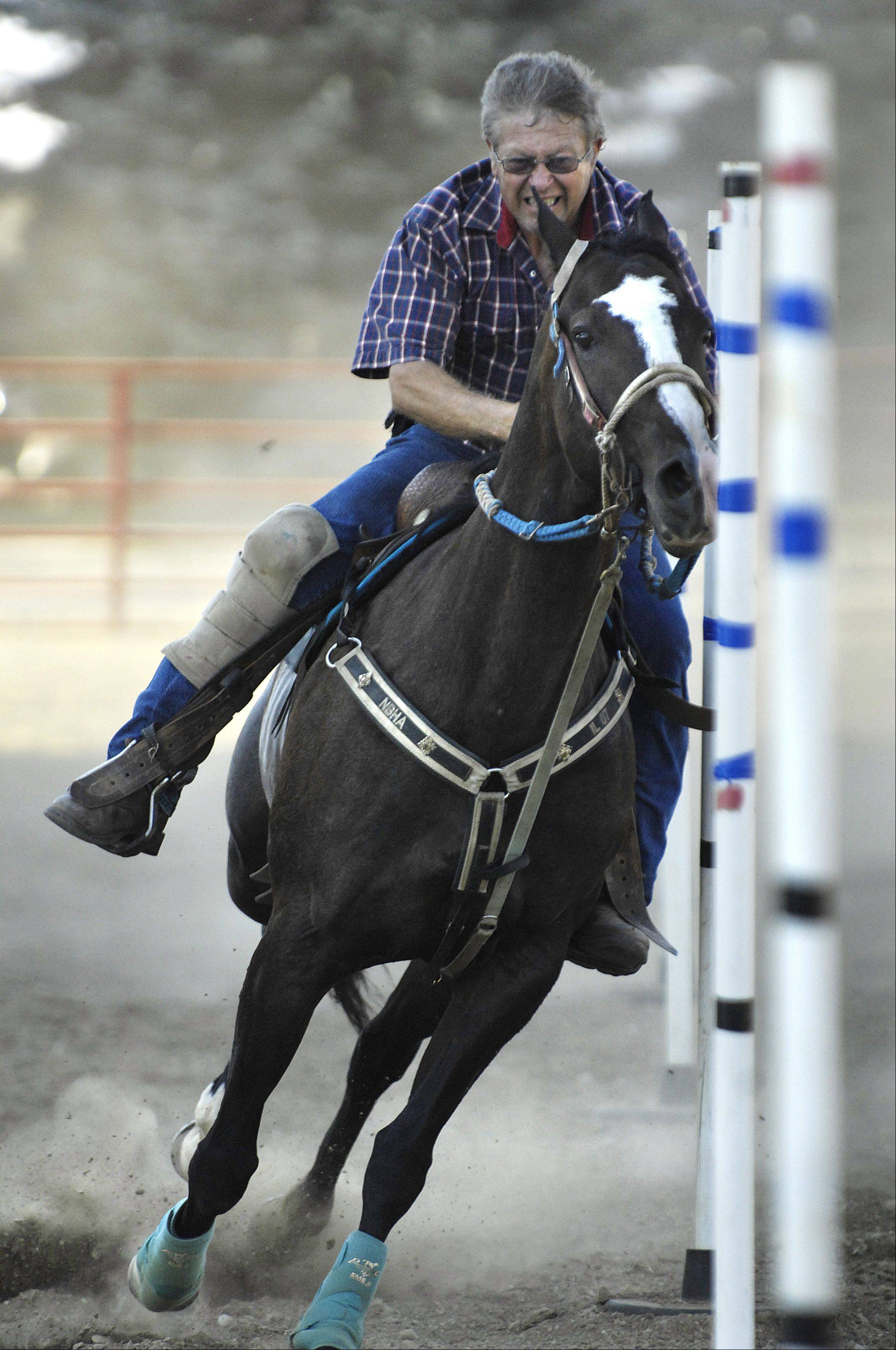 Chuck Springer of Byron steers his horse through a pole bending competition in the grandstand arena.