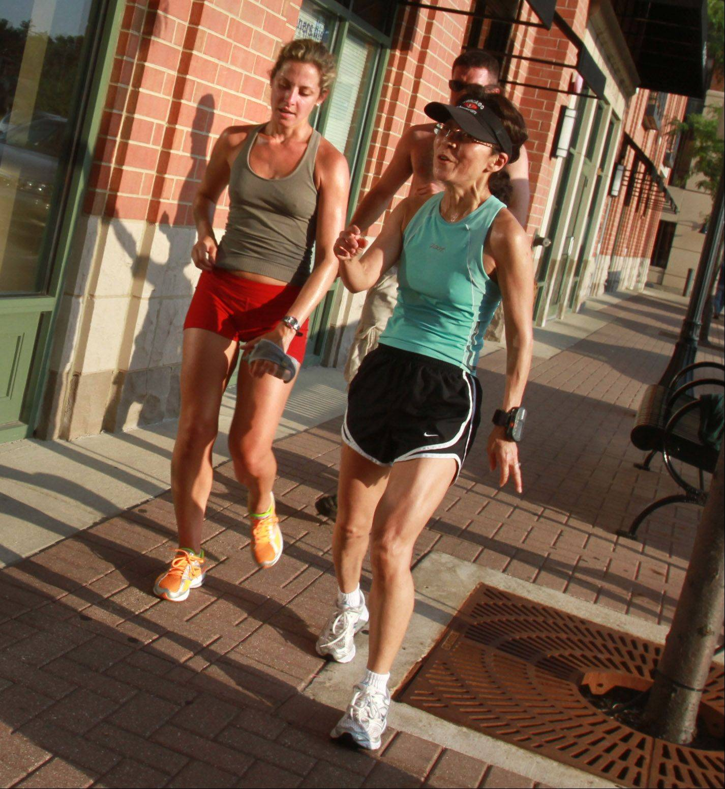 Daily Herald reporter Kerry Lester, left, and Grace Wasielewski of Prospect Heights end their five-mile run Tuesday.