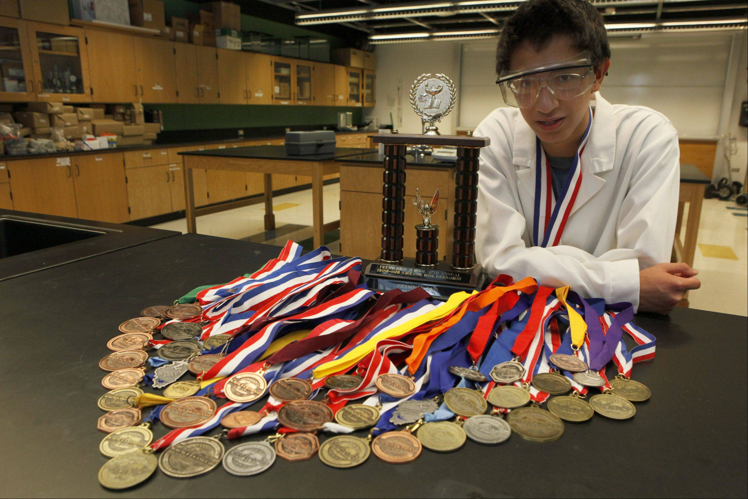 Nolan Maloney of Naperville, an incoming senior at the Illinois Mathematics and Science Academy, shows off the 44 science medals he's won since junior high school. Nolan was one of 20 semifinalists for the U.S. chemistry team this year.
