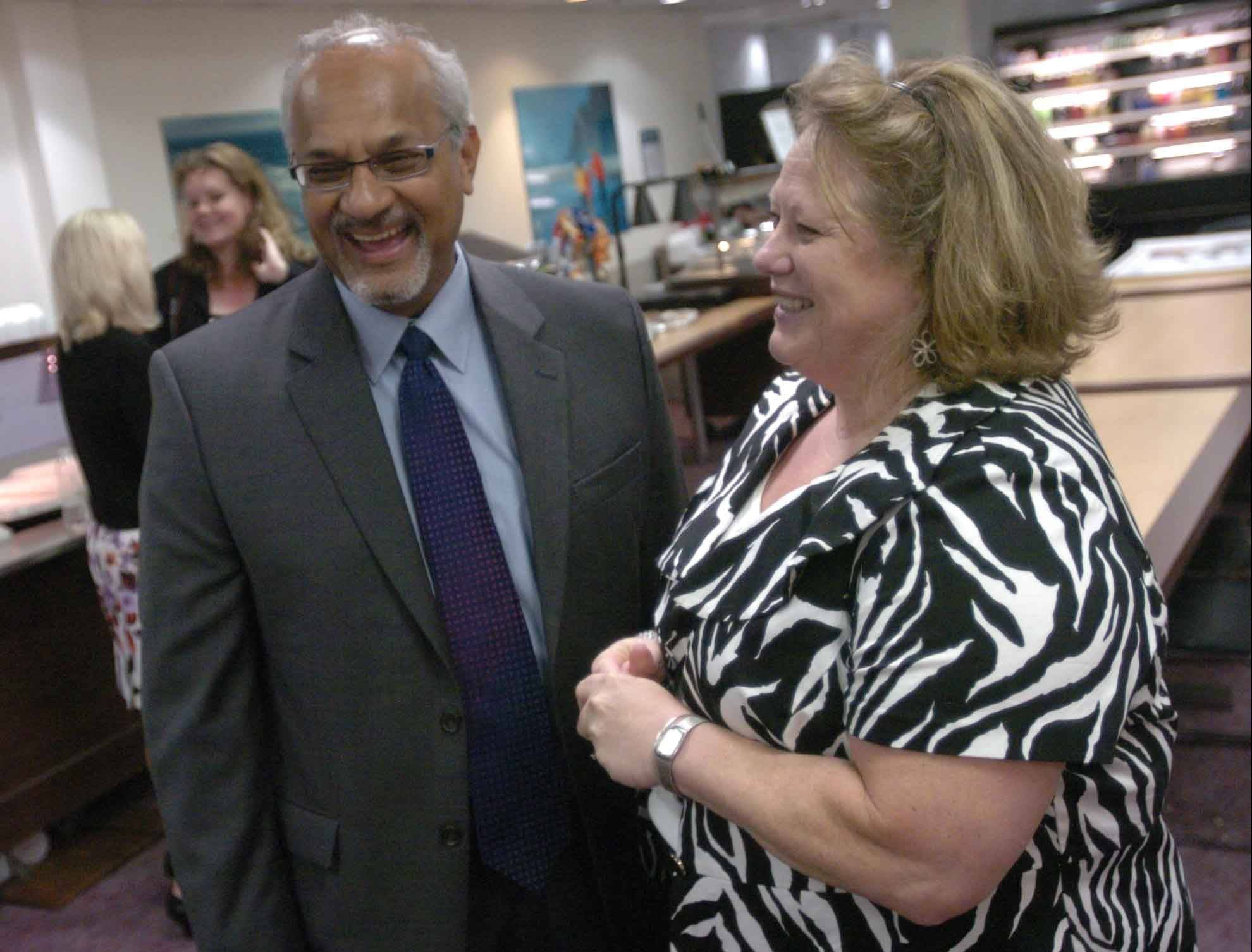 Adventist GlenOaks Hospital CEO Brinsley Lewis is leaving after 12 years as head of the Glendale Heights hospital. He shares a laugh with Tina Johnson, the hospital's community relations manager, during a farewell celebration in his honor on Wednesday.