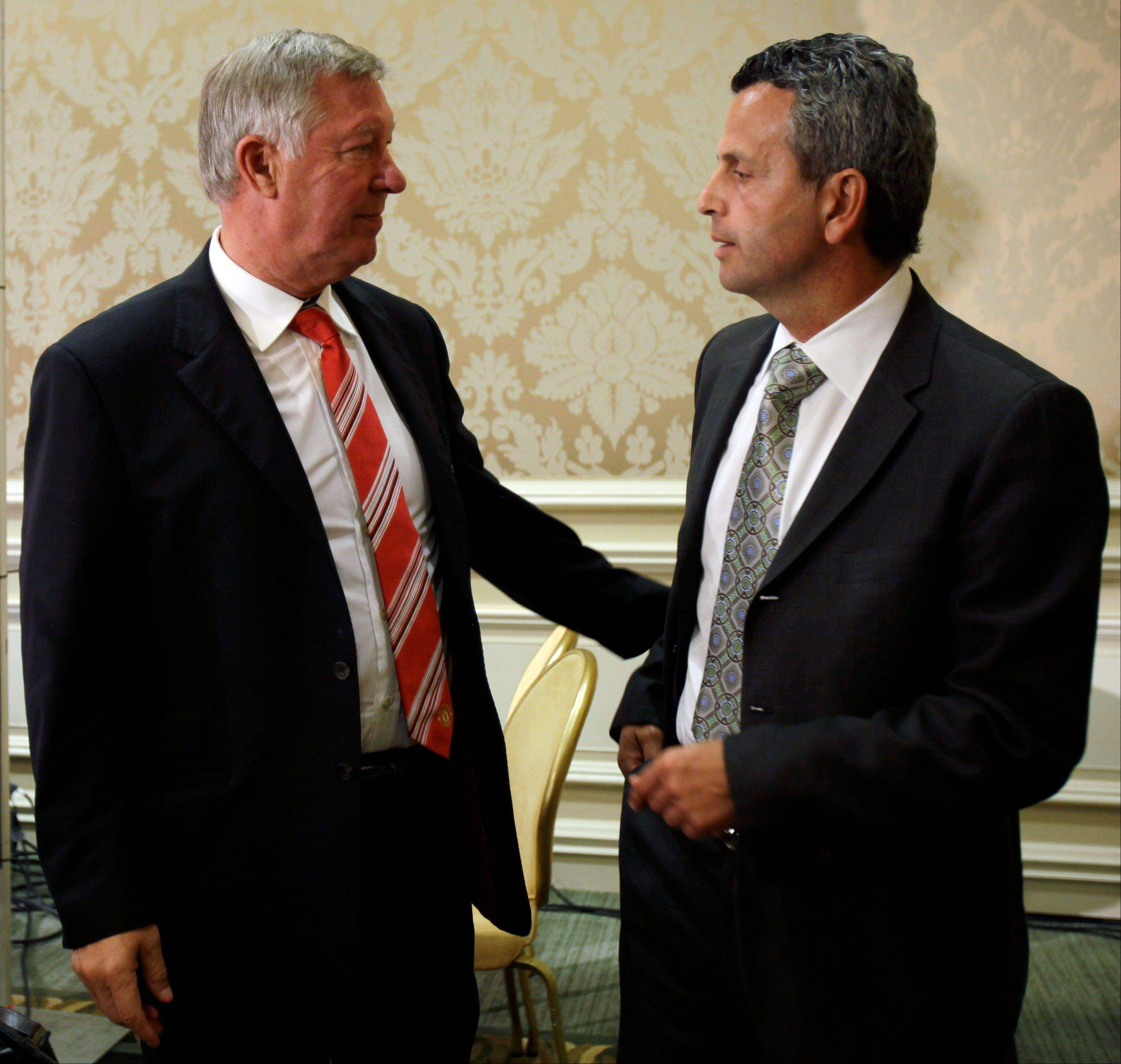 Manchester United manager Alex Ferguson, left, talks with Chicago Fire interim coach Frank Klopas after a news conference Thursday in Chicago.