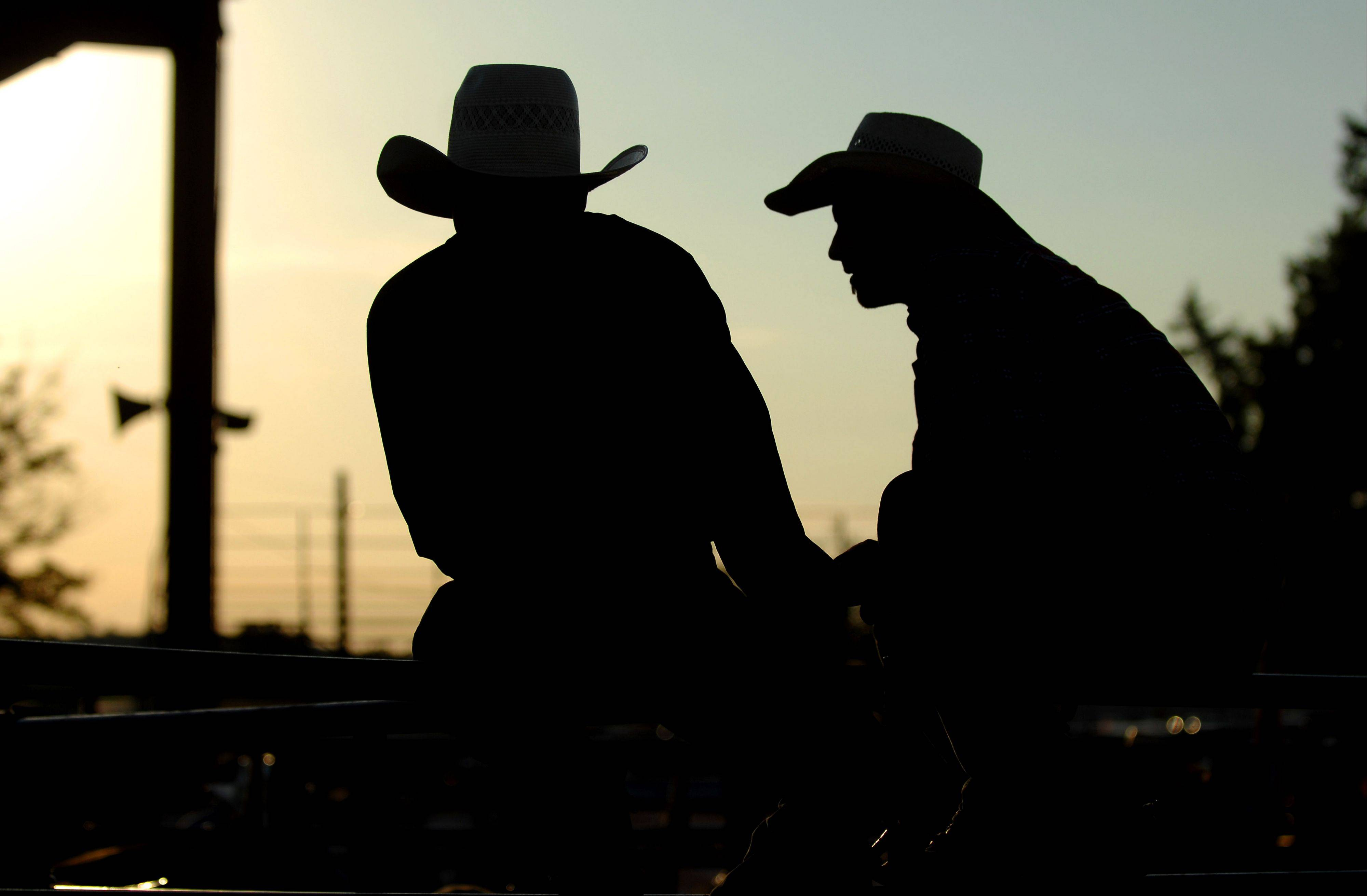 Riders Brett Olmstead, left, and Brad Check wait for the start of the Professional Championship Bullriders tour stop at the Kane County Fair in St. Charles Friday.