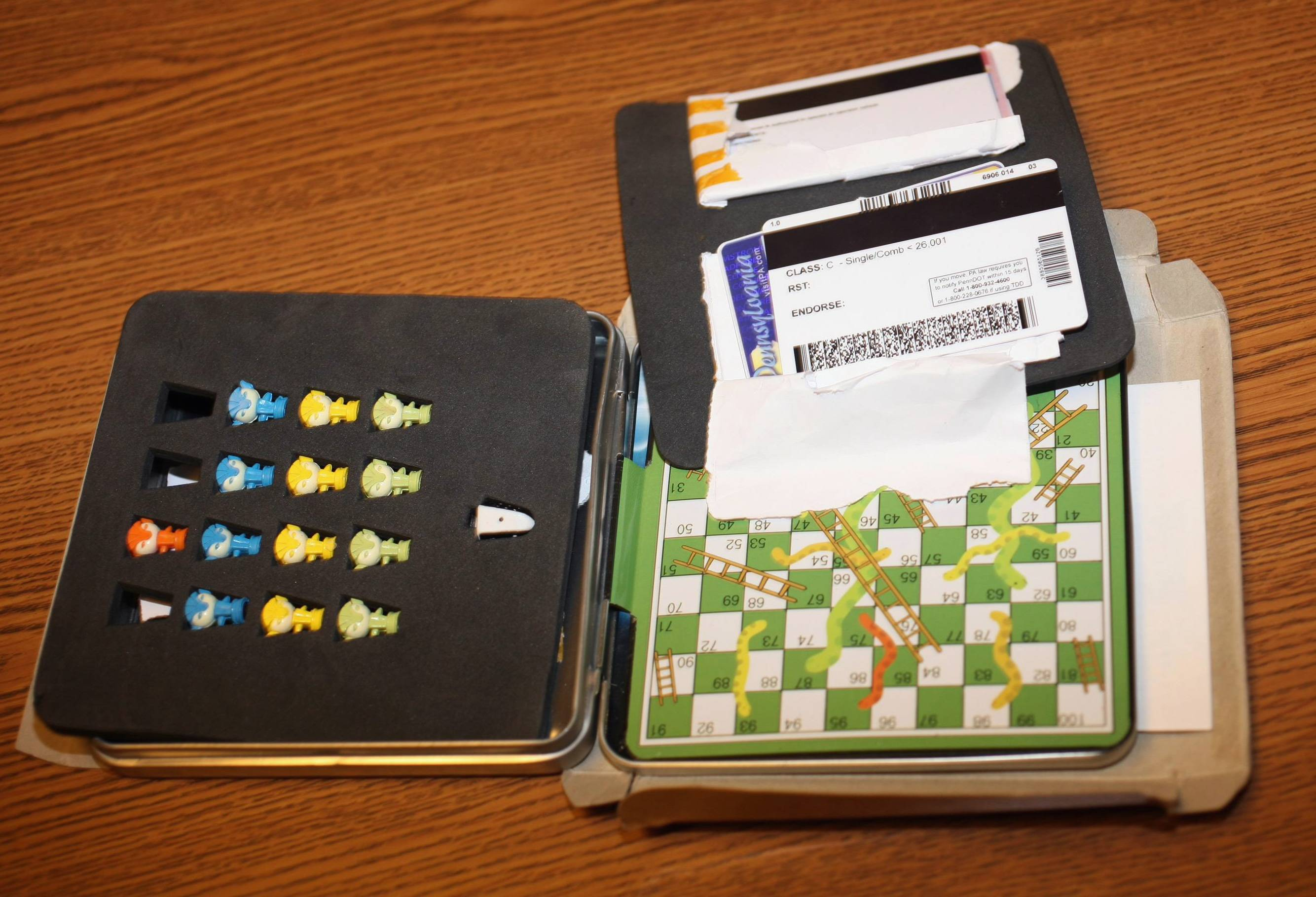 This photo provided by the Cook County Sheriff's Office shows a counterfeit driver's license hidden inside a game shipped from China. At a news conference Friday in Chicago, Sheriff Tom Dart said 1,700 counterfeit drivers's licenses were seized by Customs agents after being shipped earlier this year from China. Dart said 40 young people between the ages of 17 and 20 years old have been charged with buying the fake IDs.