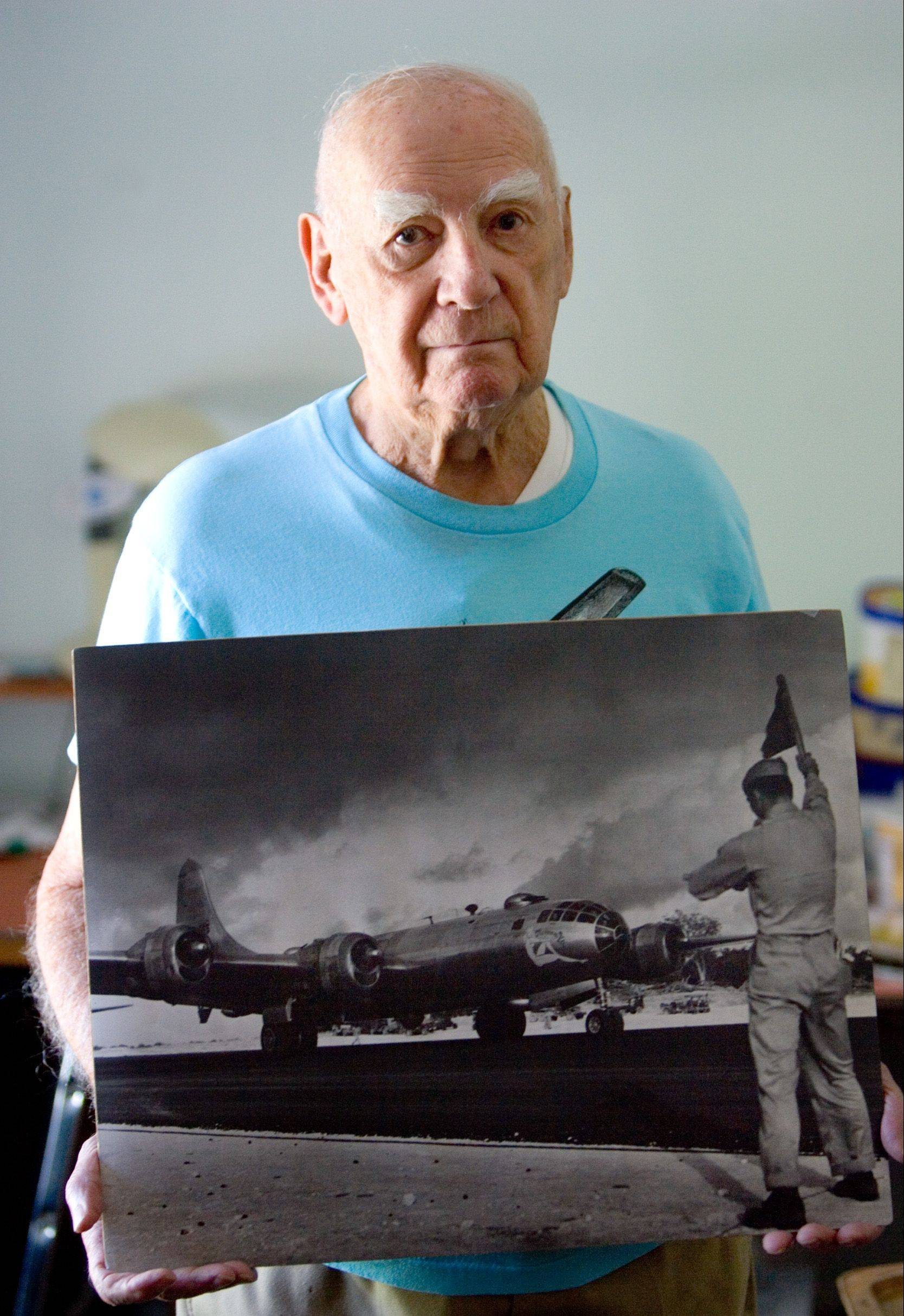 World War II veteran Joe Chovelak holds a photo of the B-29 bomber he flew during the war. Chovelak flew 35 missions as a radio operator in the Pacific Theater.