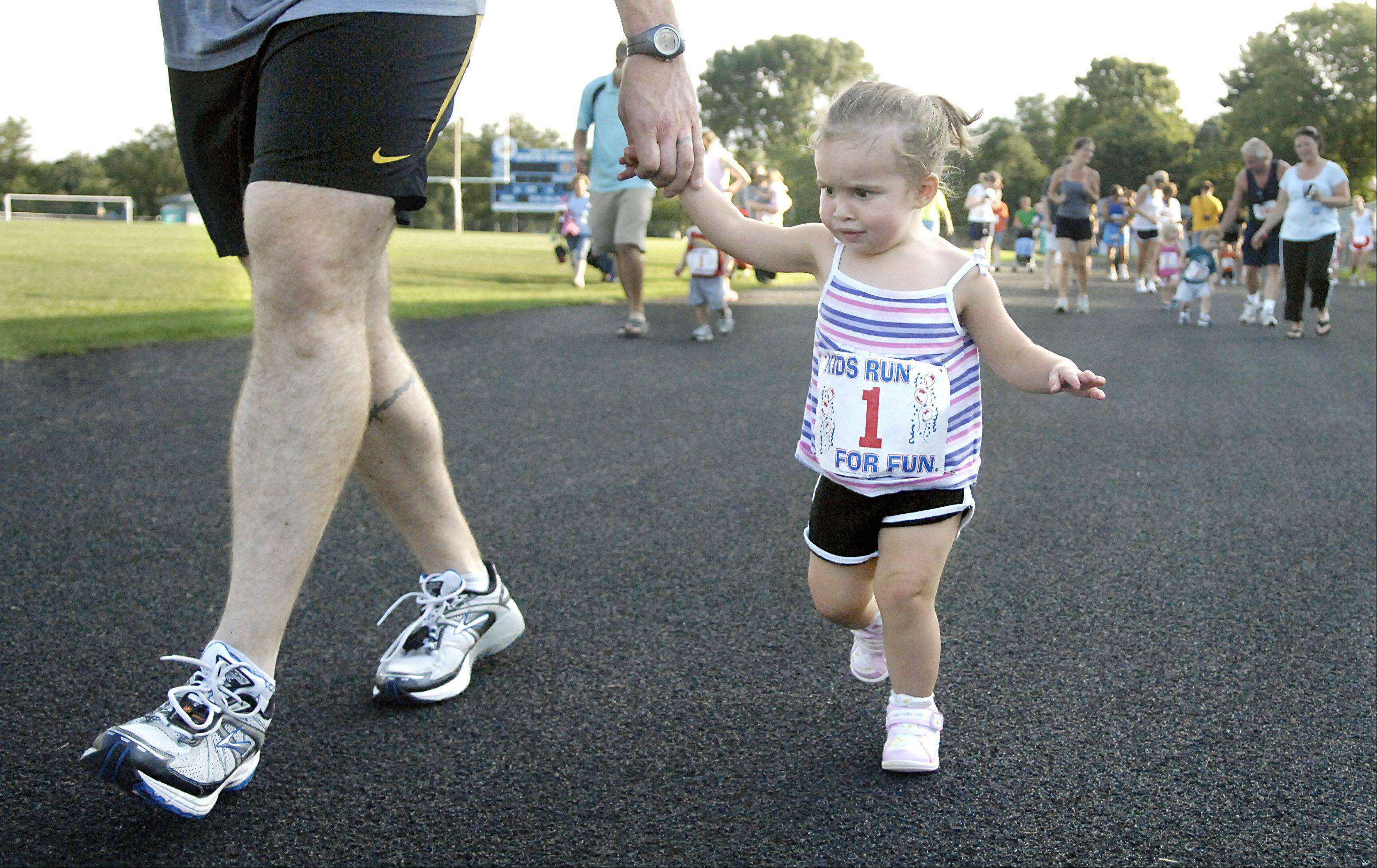 MacKenzie Schroeder, 2, of DeKalb, and her dad, Shaun, near the finish line in the Toddler Trot at the 13th annual Viking Summer Sunset Races.