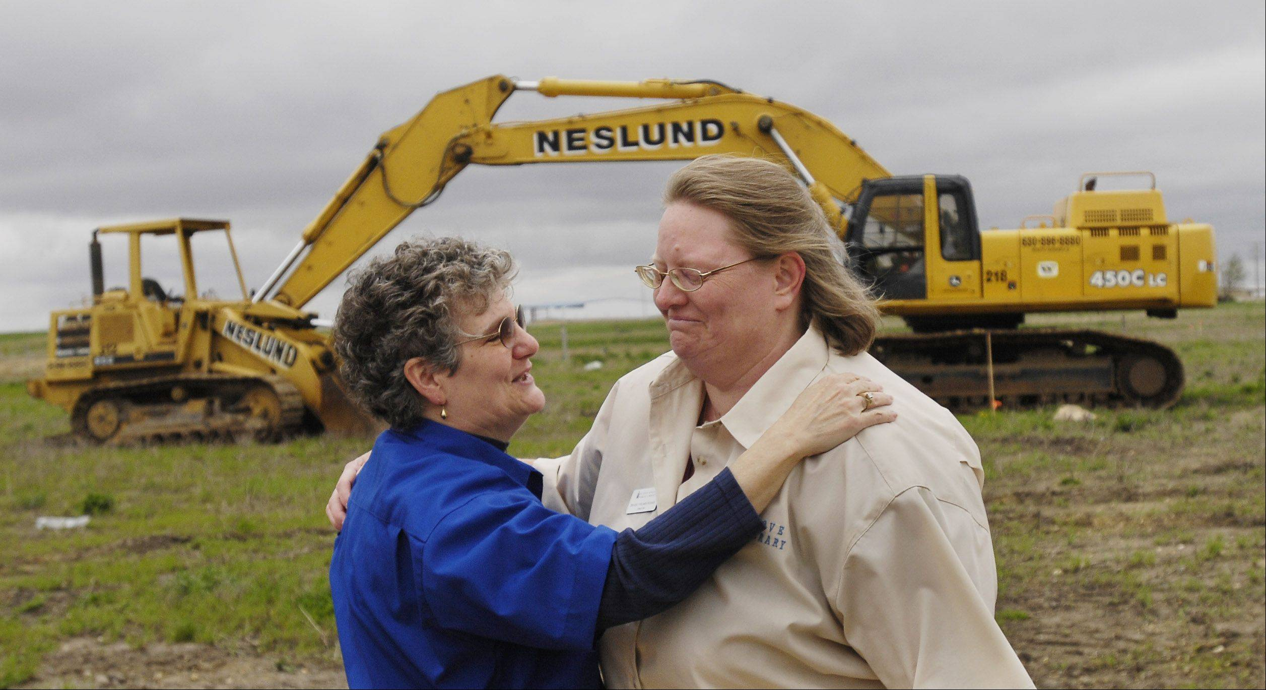 Library Director Beverly Holmes Hughes, right and circulation Director Michelle Drawz, share an emotional moment during groundbreaking ceremonies for the new Sugar Grove Library. Hughes was fired July 14.