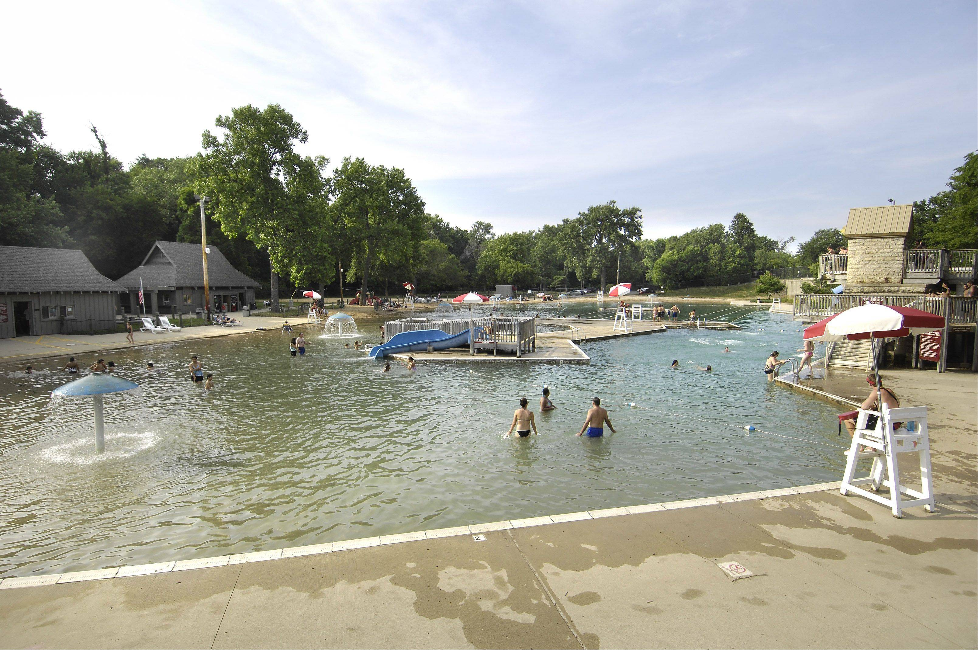 Swimmers enjoy Harold Hall Quarry Beach in Batavia Monday. The Batavia Park District is seeking bids for repairs that would prevent water from leaking out.