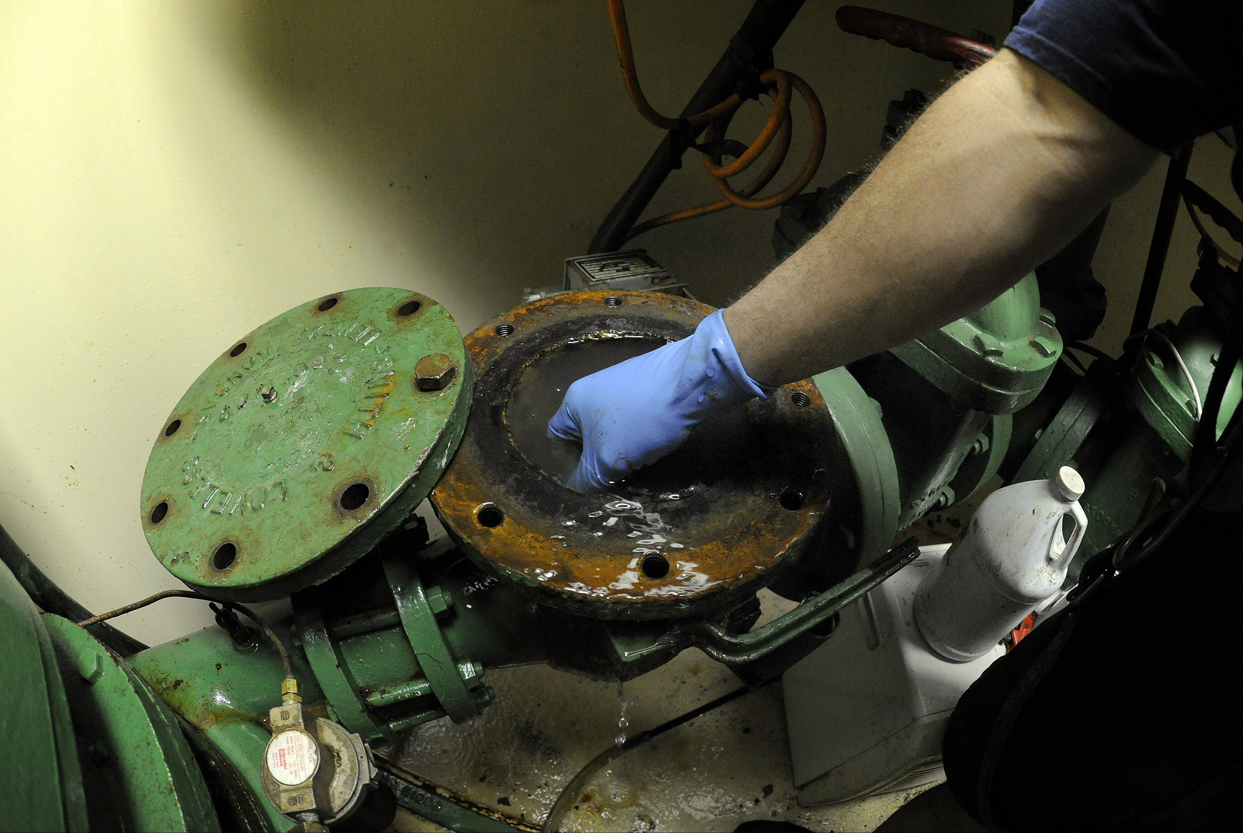 Geoff Smith cleans out a malfunctioning pump 50 feet underground at the Honeywell lift station for raw sewage, using his hand to remedy the problem area.