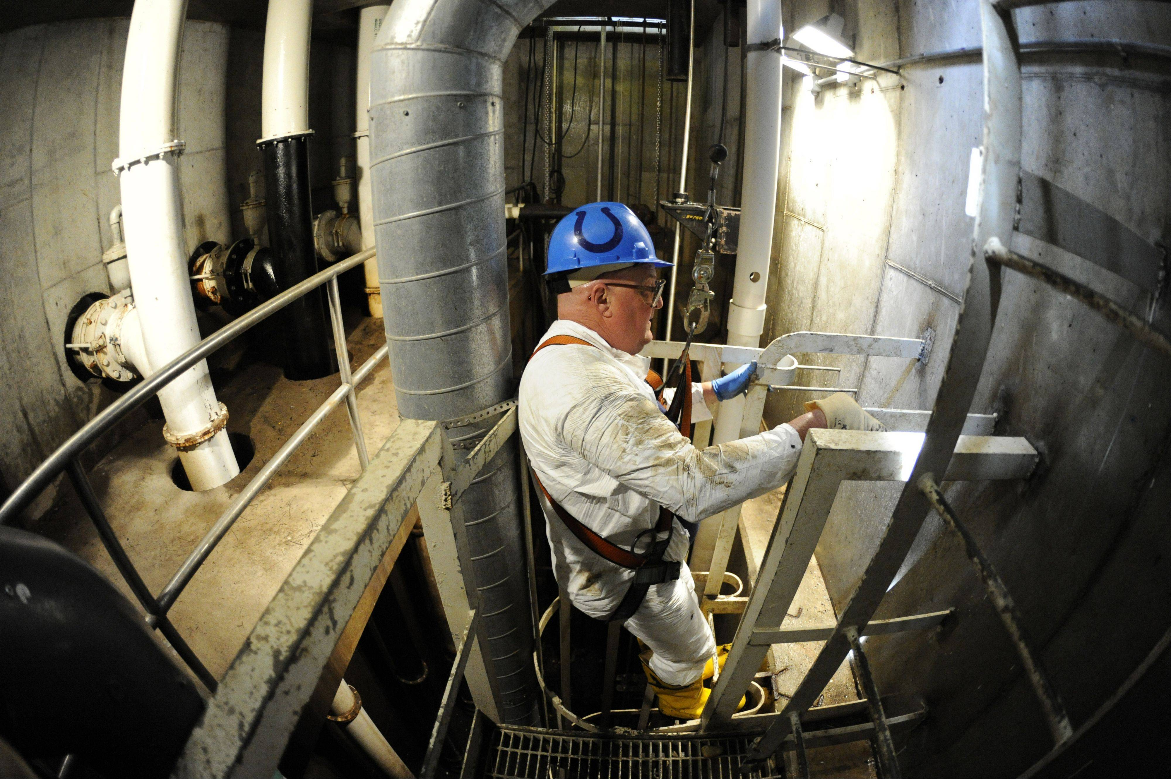 McNamara climbs down almost 40 feet underground into the storm water station located on the border of Arlington Heights and Mount Prospect getting ready to clean out around the pumps.