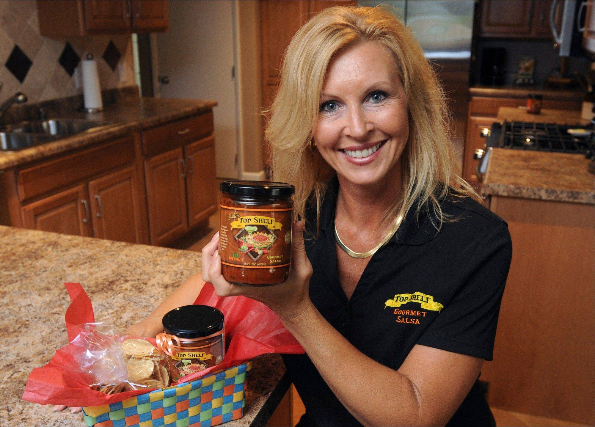 Jodi Haxmeier, of Moline Ill, shows off a jar of Jodi�s Top Shelf Gourmet Salsa. Two Hy-Vee stores started carrying Top Self Salsa in March, and now it�s available at 19 Hy-Vee locations.