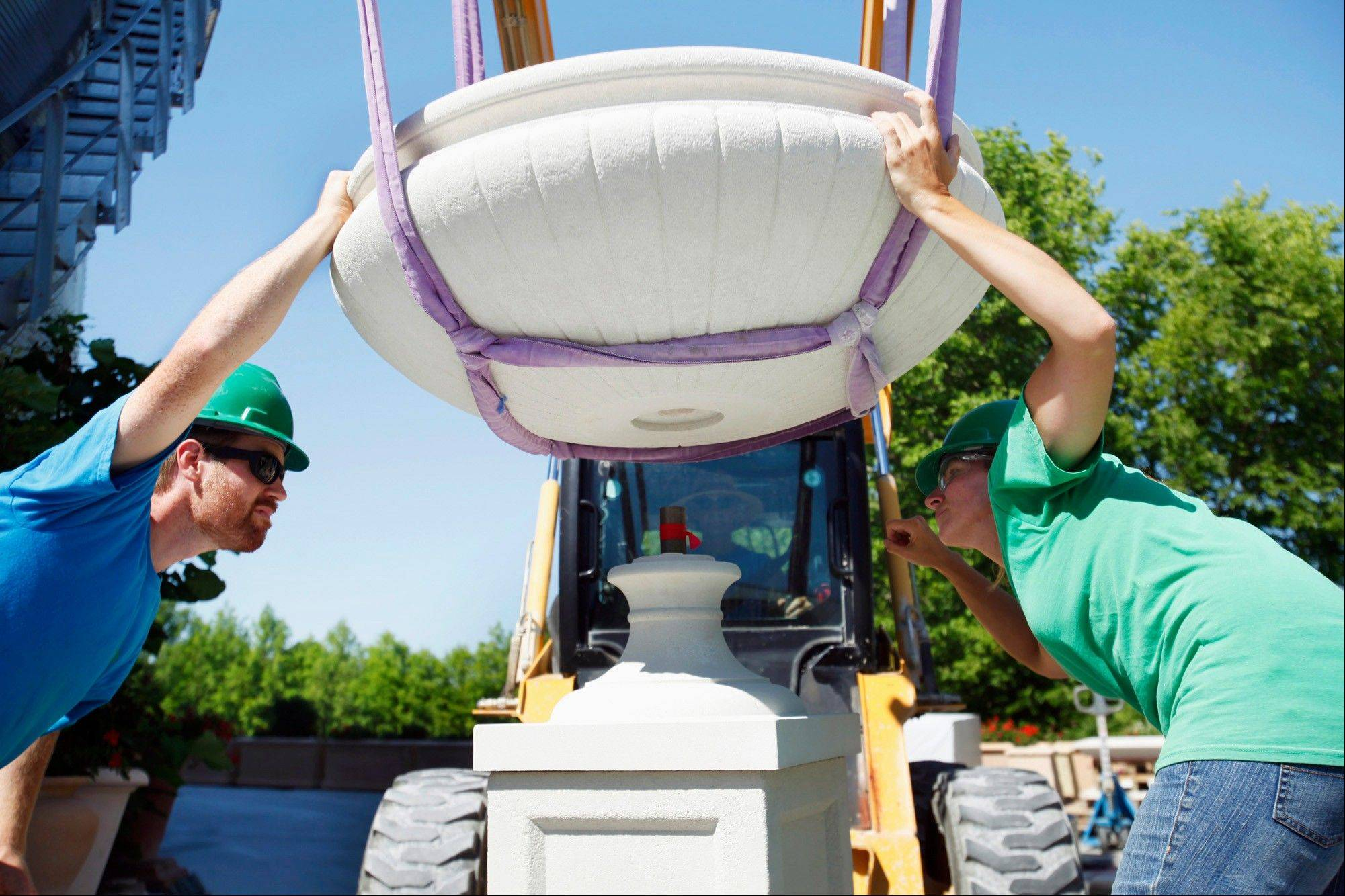 Andrew Abbott, left, and Shari Smiley carefully position a planter over the base as it is lowered into place at Classic Garden Ornaments Ltd., also known as Longshadow in Pomona, Ill.