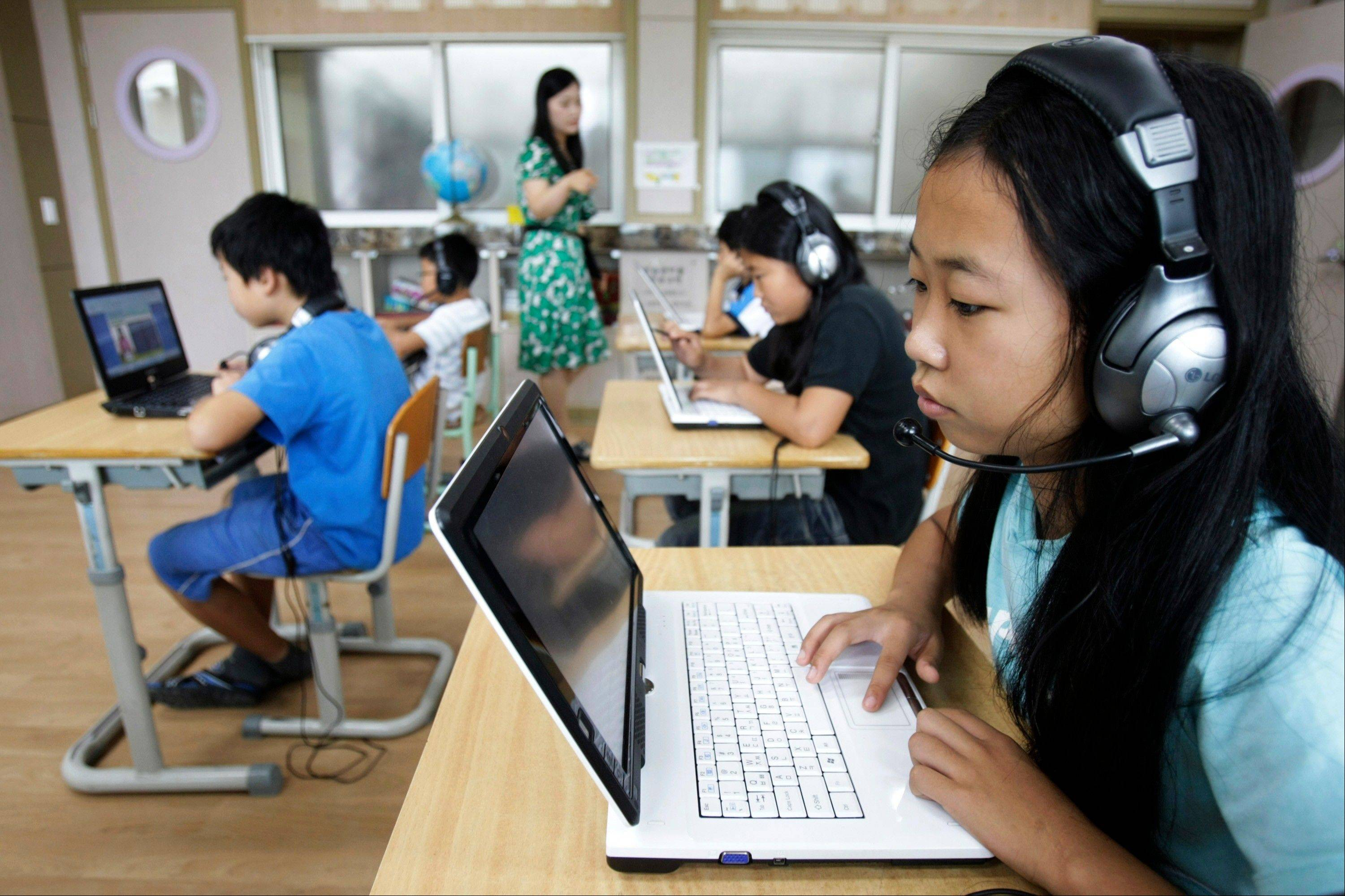 South Korean student Jang Woo-dam, right, and her classmates use tablet PCs to study in a class at Sosu Elementary School in Goesan, South Korea. The country is taking a $2 billion gamble that its students are ready to ditch paper textbooks in favor of tablet PCs as part of a vast digital scholastic network.