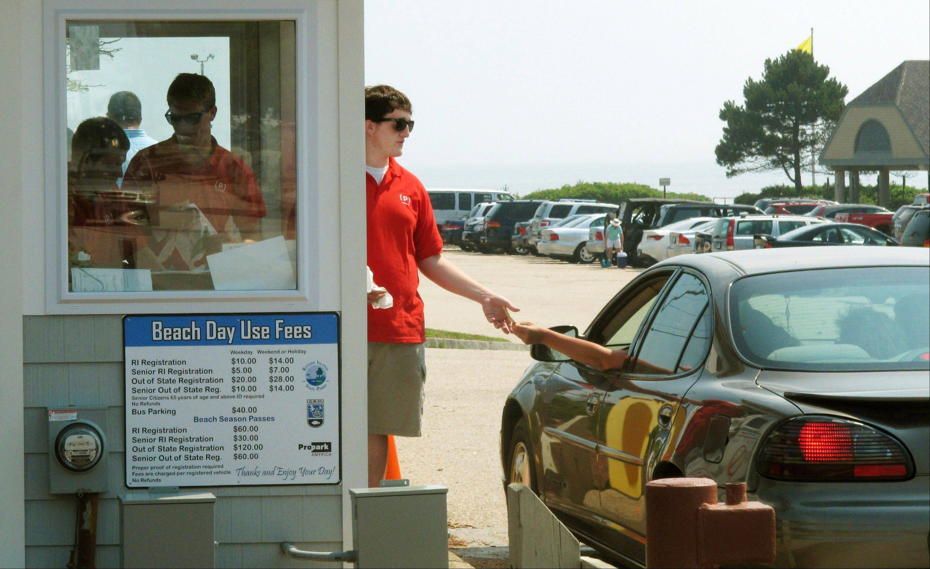 An attendant at Scarborough State Beach collects an entrance fee from a beach-goer in Narragansett, R.I. The state of Rhode Island has nearly doubled the fees to park at some of its state beaches this year.