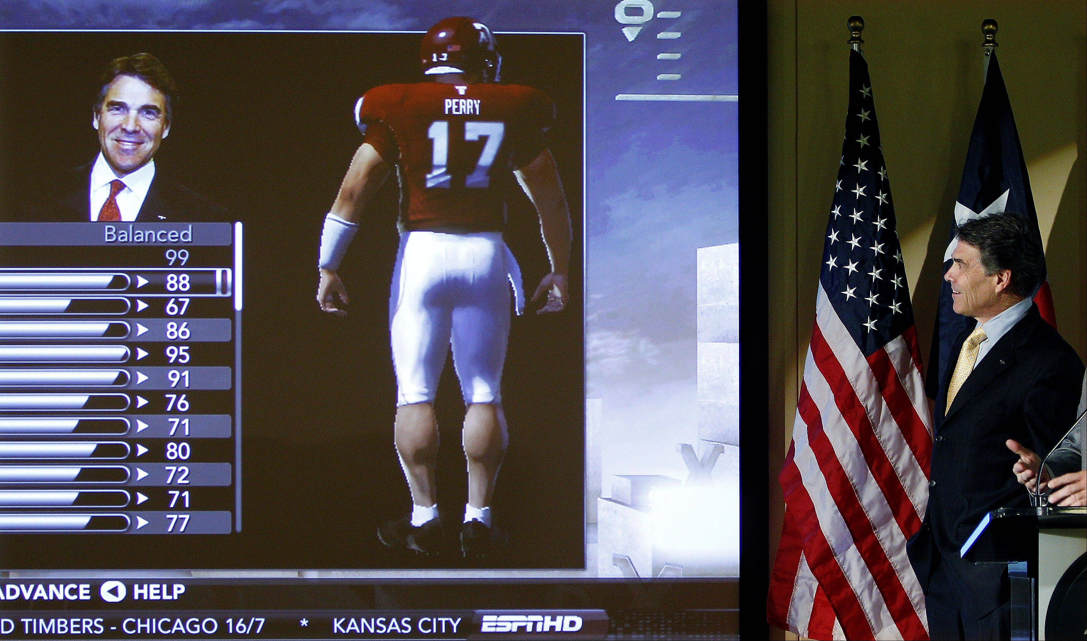 Texas Gov. Rick Perry, right, is featured in an electronic football game during a news conference Monday at Electronic Arts BioWare in Austin. Officials announced they are expanding their EA Sports division and adding 300 jobs in central Texas.