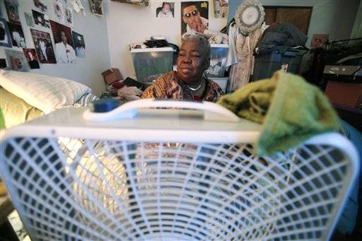 Mary Ware sits still on her bed next to the fan while waiting for a ride for dialysis July 21 in Chicago. Ware, 62, who suffers from high blood pressure and diabetes and requires dialysis three times a week, lives in a basement Chicago apartment with her son and daughter. She receives disability income but can't afford air-conditioning. Thousands of low-income people across the nation are having trouble paying their electric bills during this sweltering summer because the assistance normally available isn't there after Congress cut millions of dollars used for the program.
