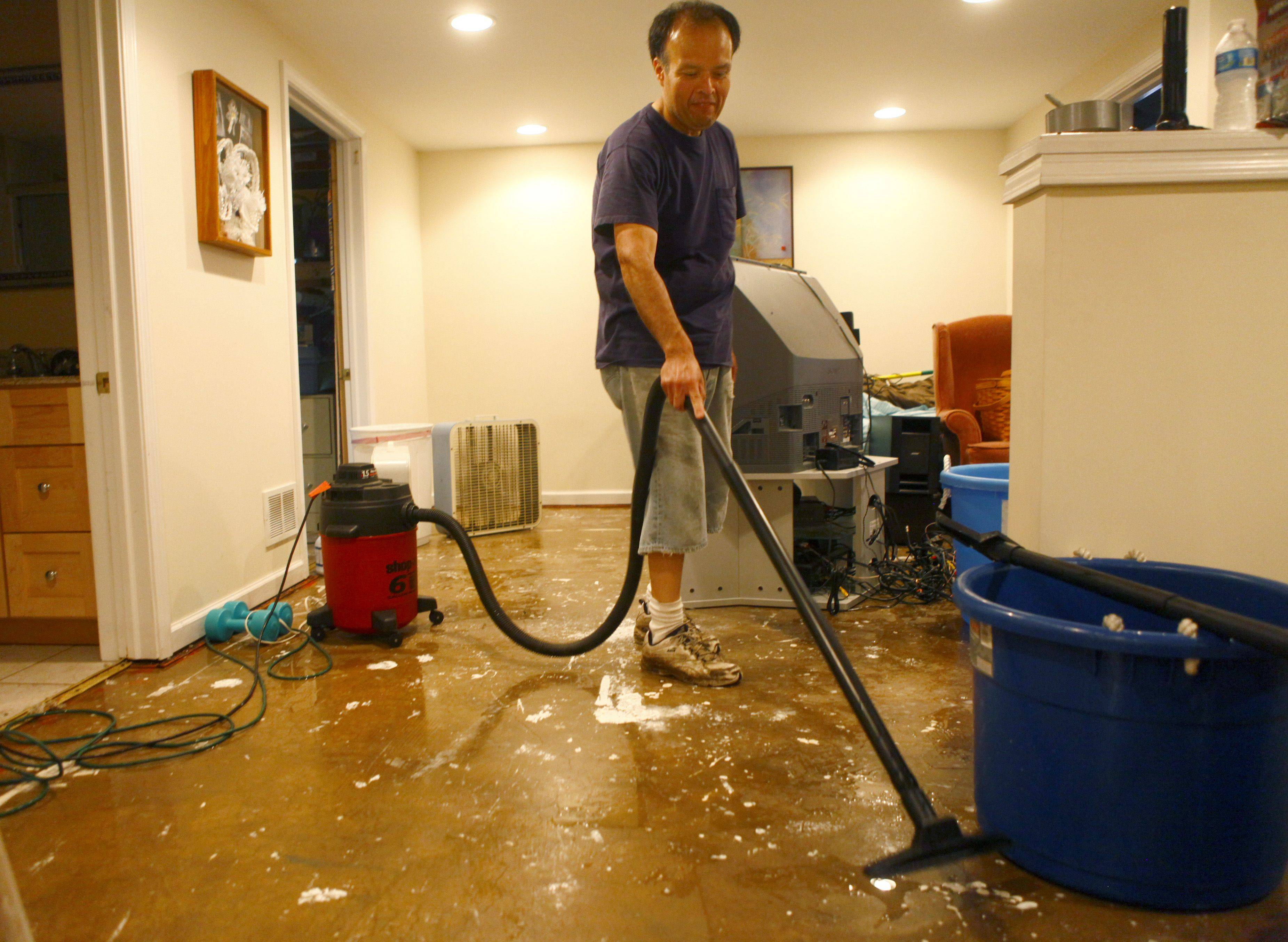 John Mesa vacuums the water off the ground in his brothers basement, in Mt. Prospect Saturday morning. There was about 6 inches of water this morning in his basment. Bill Mesa said his basement has never flooded like this before. They started the clean-up efforts at 5 this morning.