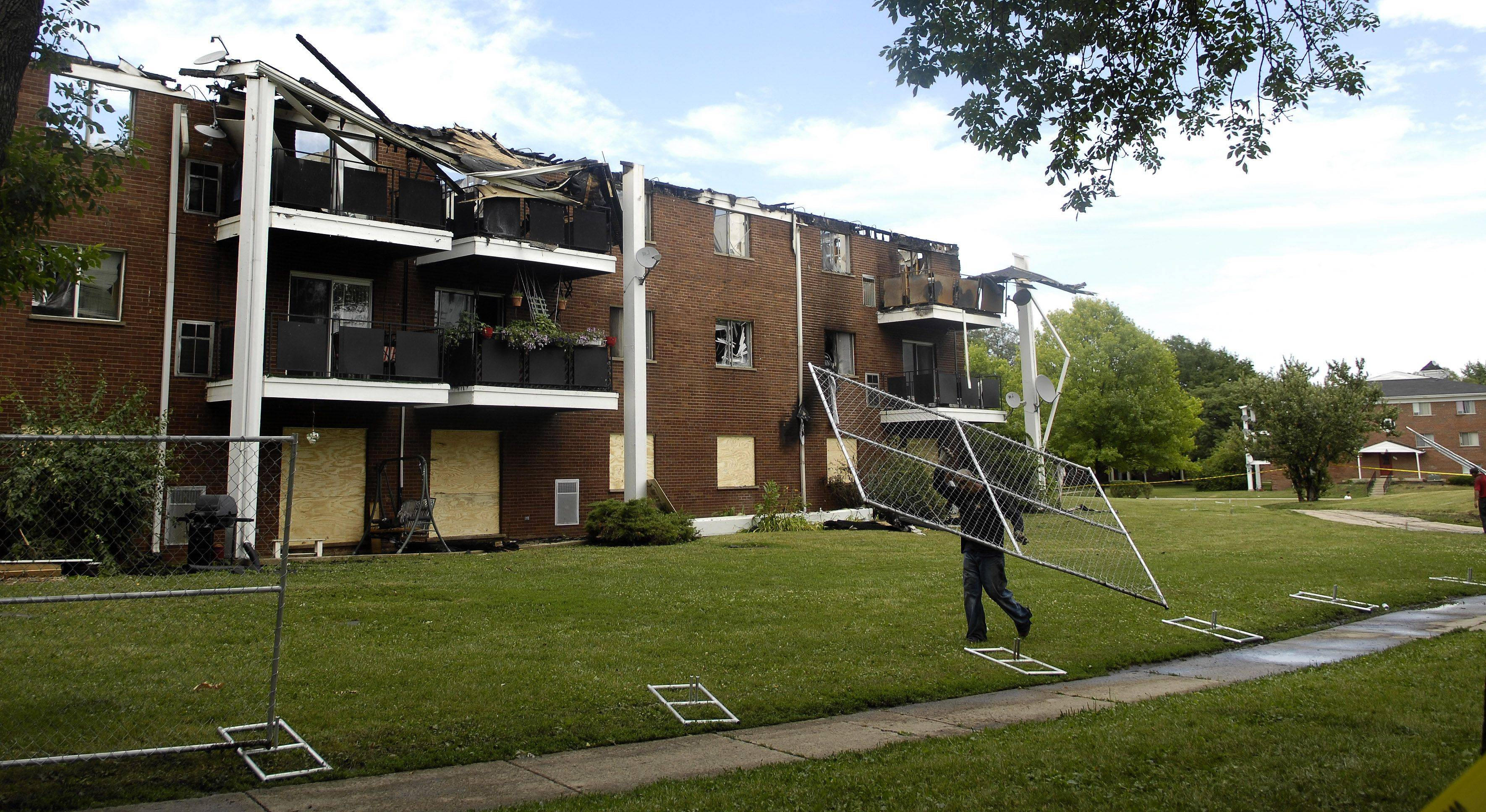 Workers install safety fences after a fire displaced residents at the Colonial Green Apartments in Mount Prospect.