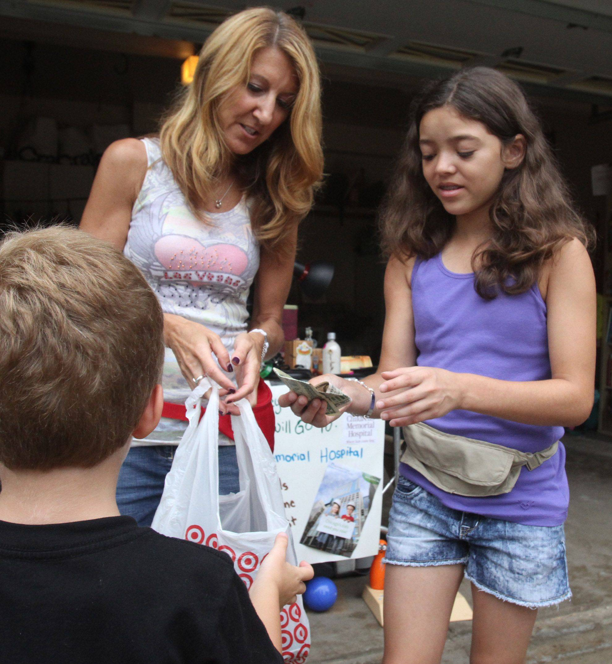 Mundelein 12-year-old Rebecca Ackerman and her mom, Michele, sells items to Christopher Elliott, 5, of Mundelein, at a garage sale Saturday the girl organized to raise money for Children's Memorial Hospital in Chicago.