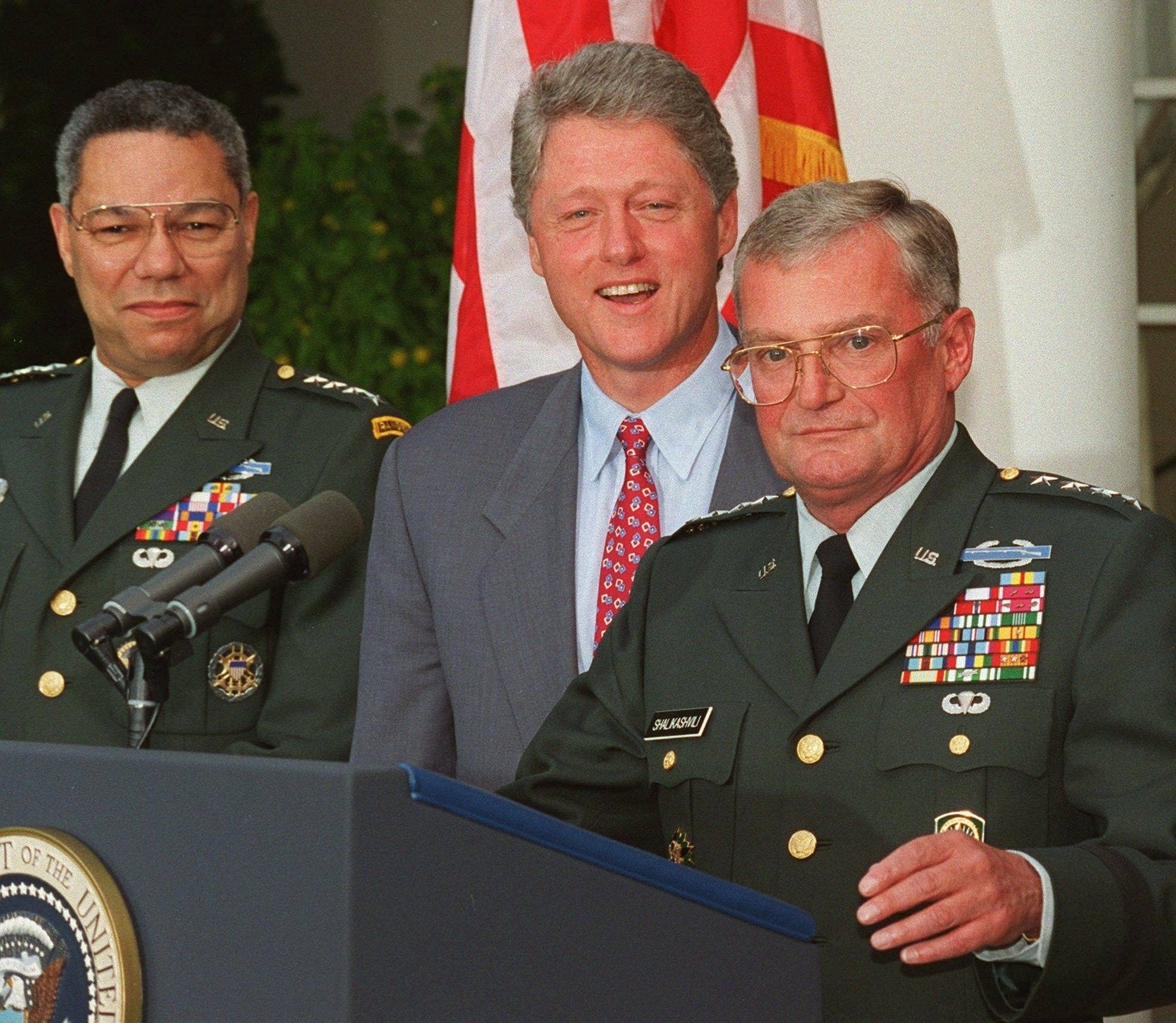 In this Aug. 11, 1993 file photo, Army Gen. John Shalikashvili speaks in the Rose Garden of the White House in Washington accompanied by President Bill Clinton and Joint Chiefs Chairman Gen. Colin Powell. On Saturday, July 23, 2011, the White House said Retired Gen. Shalikashvili, former chairman of the Joint Chiefs of Staff, has died.