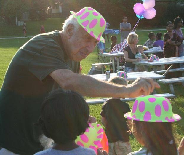 A volunteer distributes silly hats at last year�s National Night Out in Schaumburg.