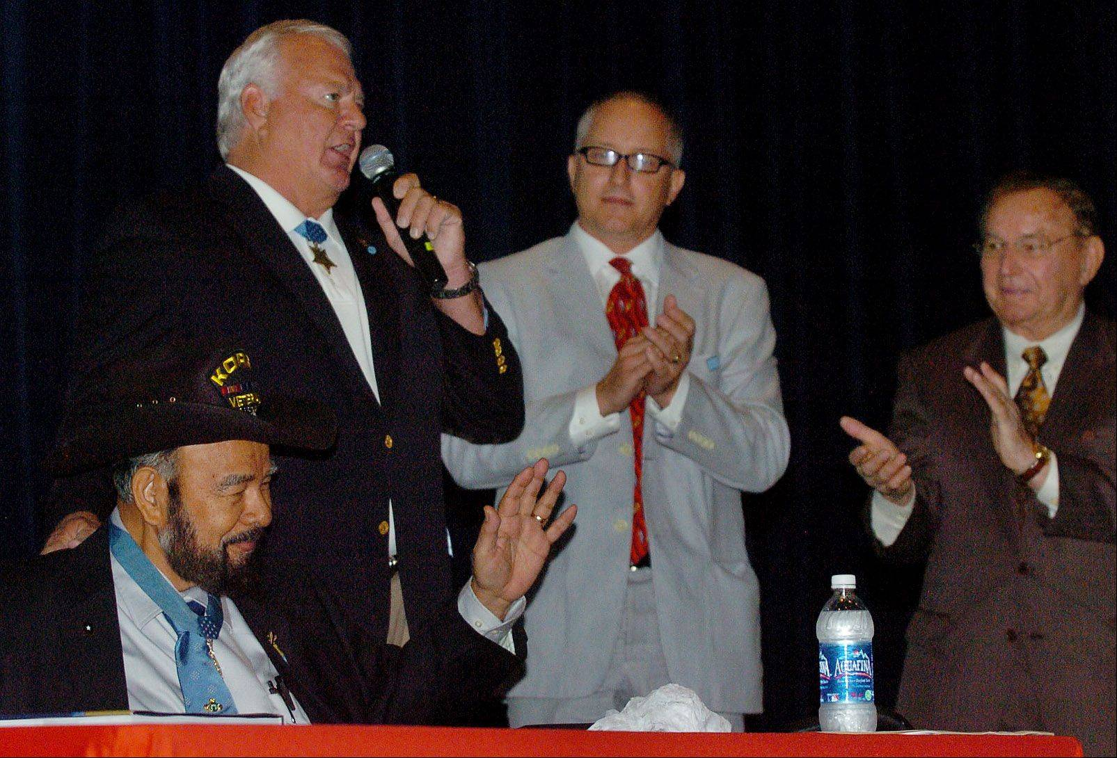 Former U.S. Army Cpl. Rodolfo Hernandez, seated, and former Navy Petty Officer Michael Thornton, with microphone, acknowledge the applause. On the right are Chip Borkowski, Medal of Honor committee volunteer and Richard L. Duchossois, of Arlington Park racetrack.