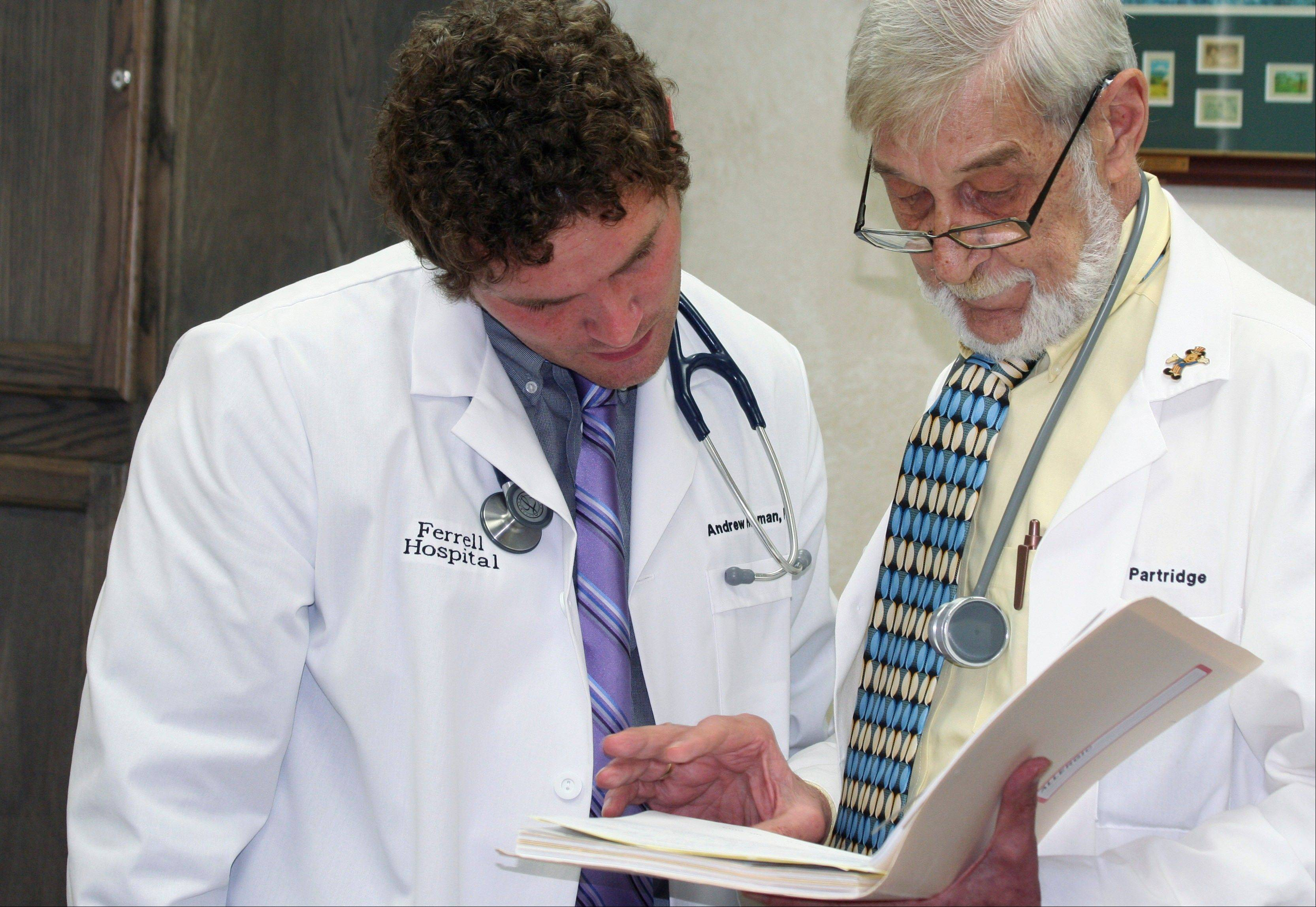 Associated Press Andrew Hosman confers on a patient�s chart with his grandfather Elliott Partridge, chief of the medical staff and chief of emergency medicine at Ferrell Hospital in Eldorado, Ill.