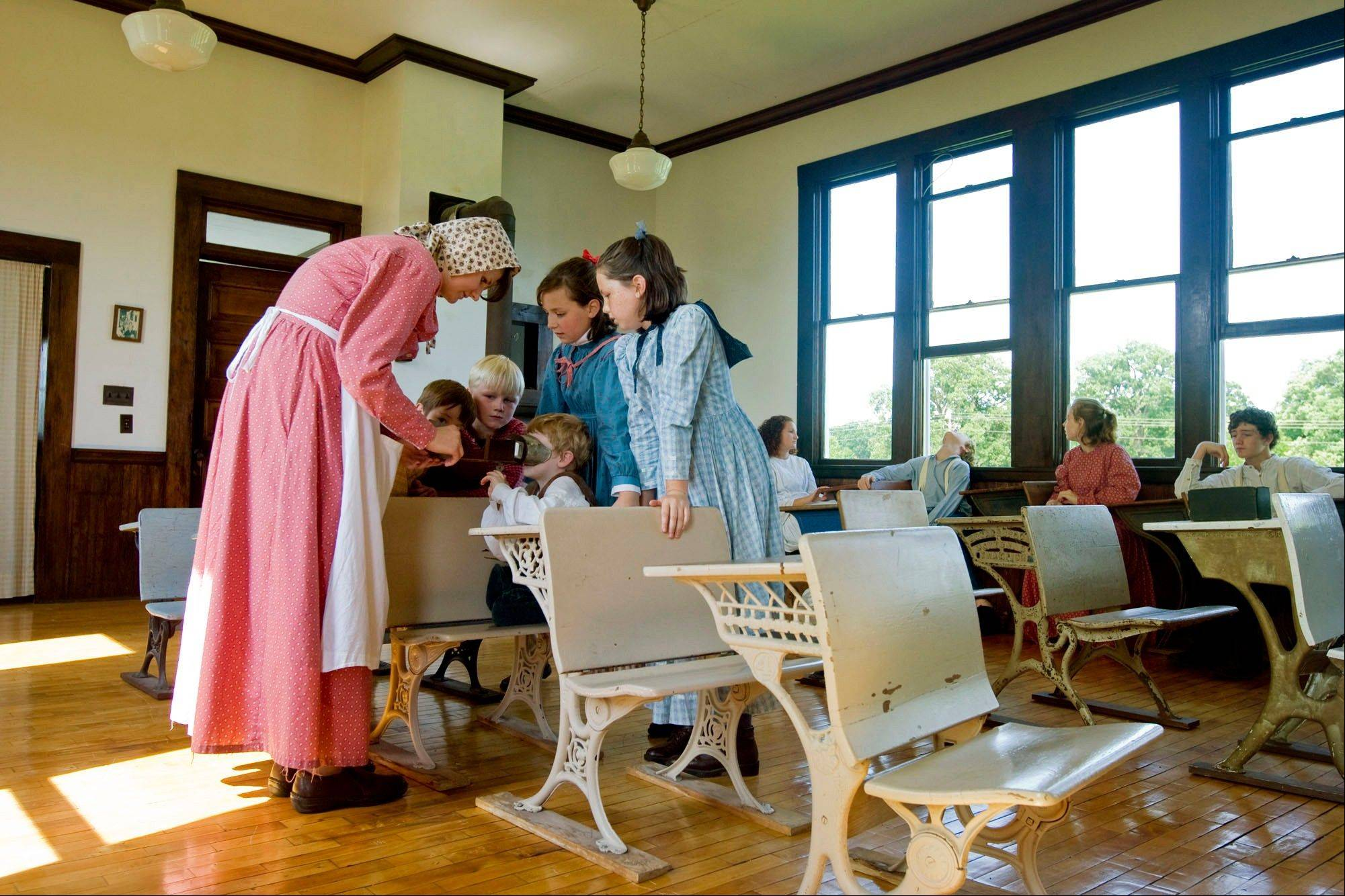 Charlotte Rayburn, left, shows an optical device to a group of children in the one-room Bethel School in June at the Friends Creek Conservation Area near Cisco, Ill. Built circa 1890, the school welcomed its last class in 1946.