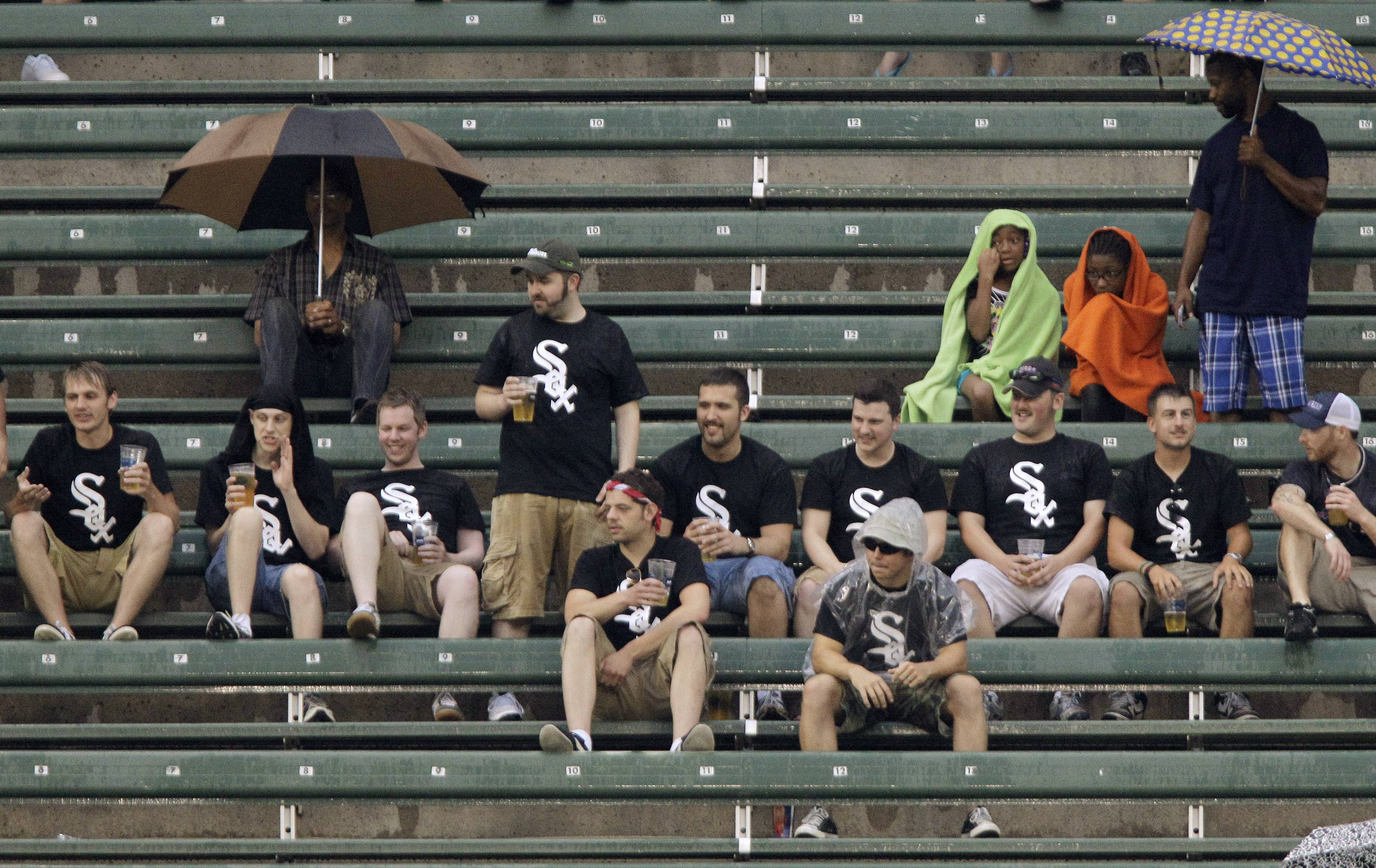 Fans wait out a rain delay before the start of a baseball game between the Cleveland Indians and the Chicago White Sox Saturday