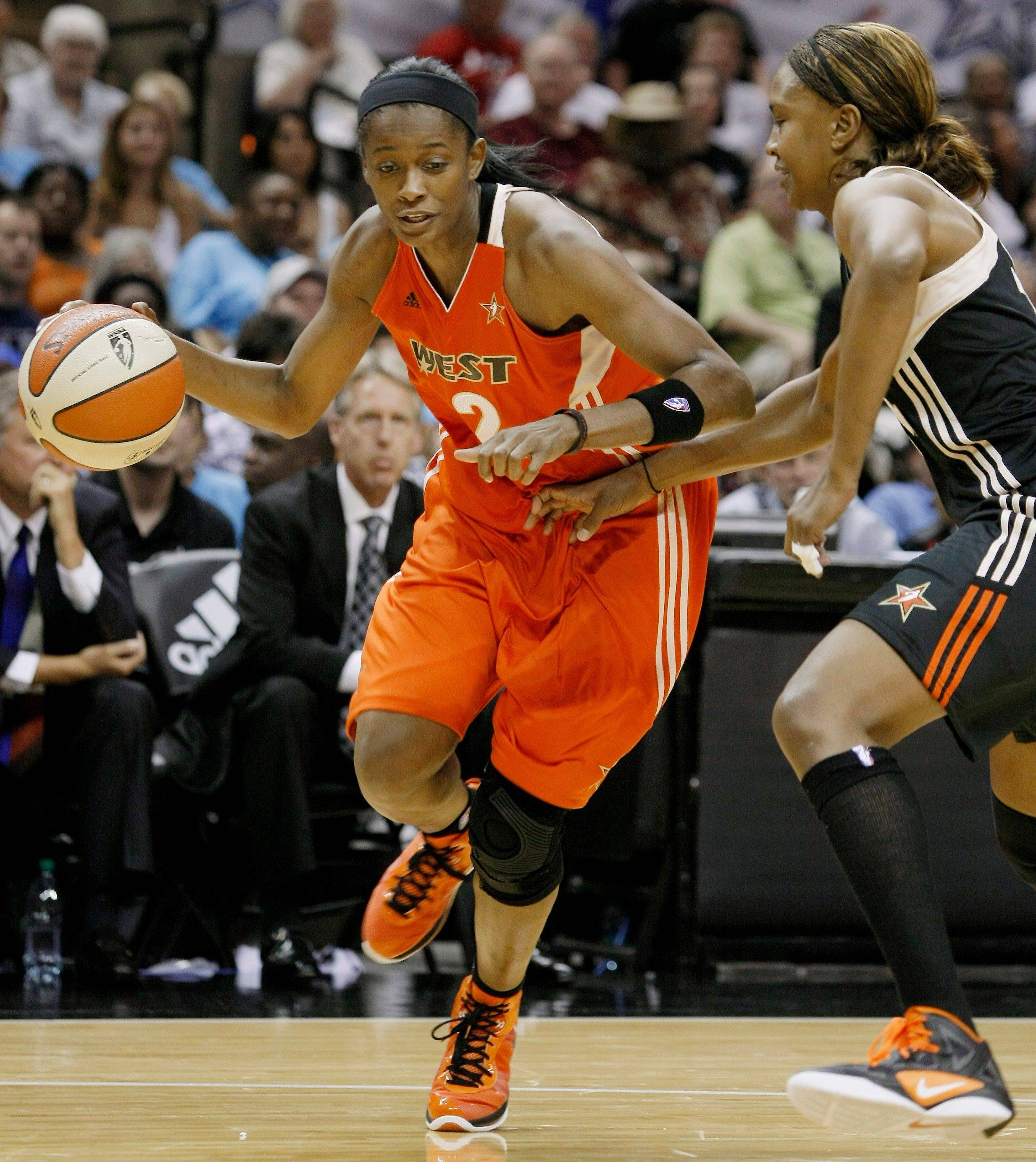 The West�s Swin Cash, left, drives around the East�s Tamika Catchings during the second half of the WNBA All-Star Game on Saturday. Cash was named MVP despite a 118-113 victory by the East.