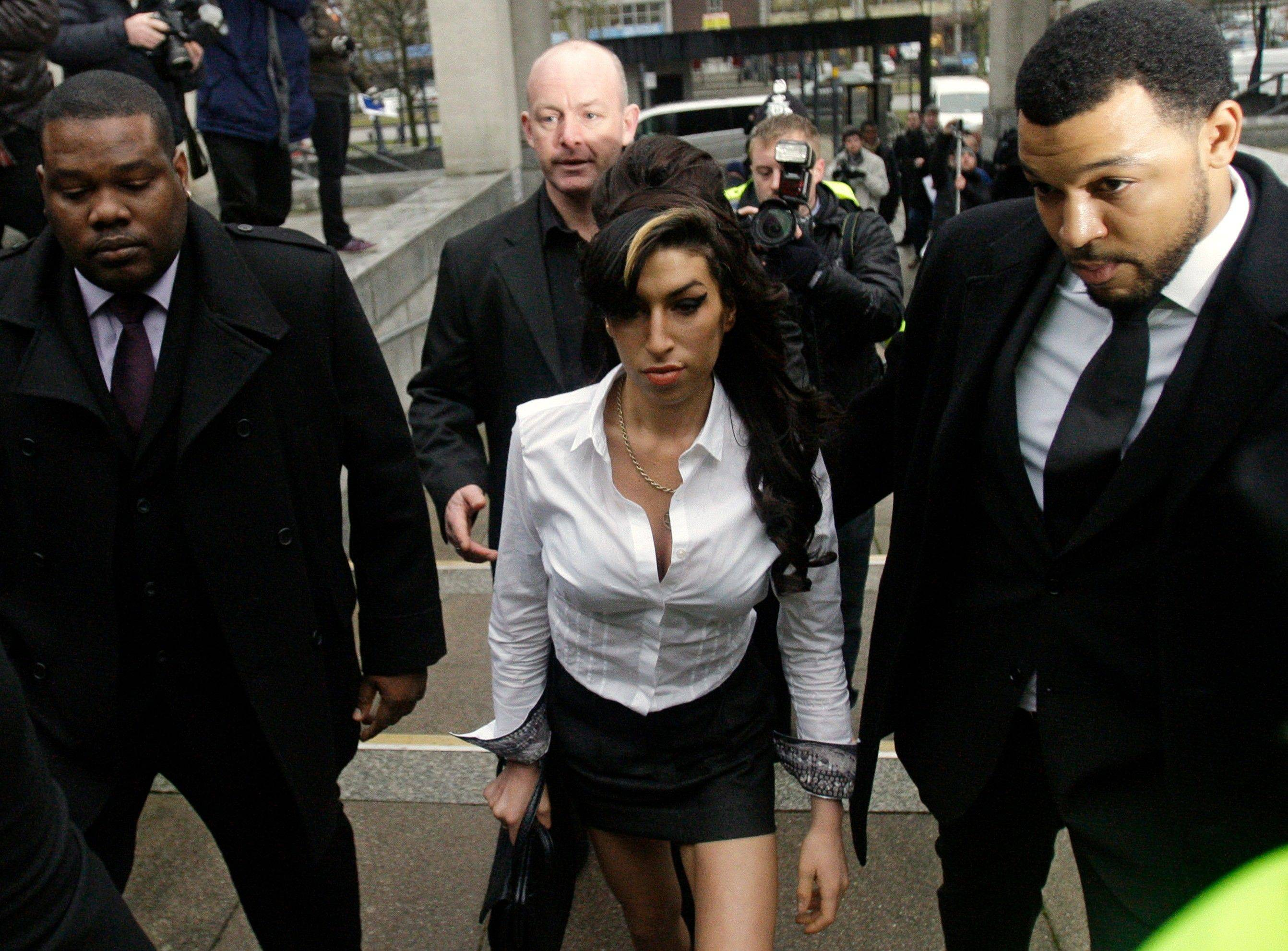 British singer Amy Winehouse, center, arrives at Magistrates Court in Milton Keynes, England where she was suing to keep the paparazzi away from her.