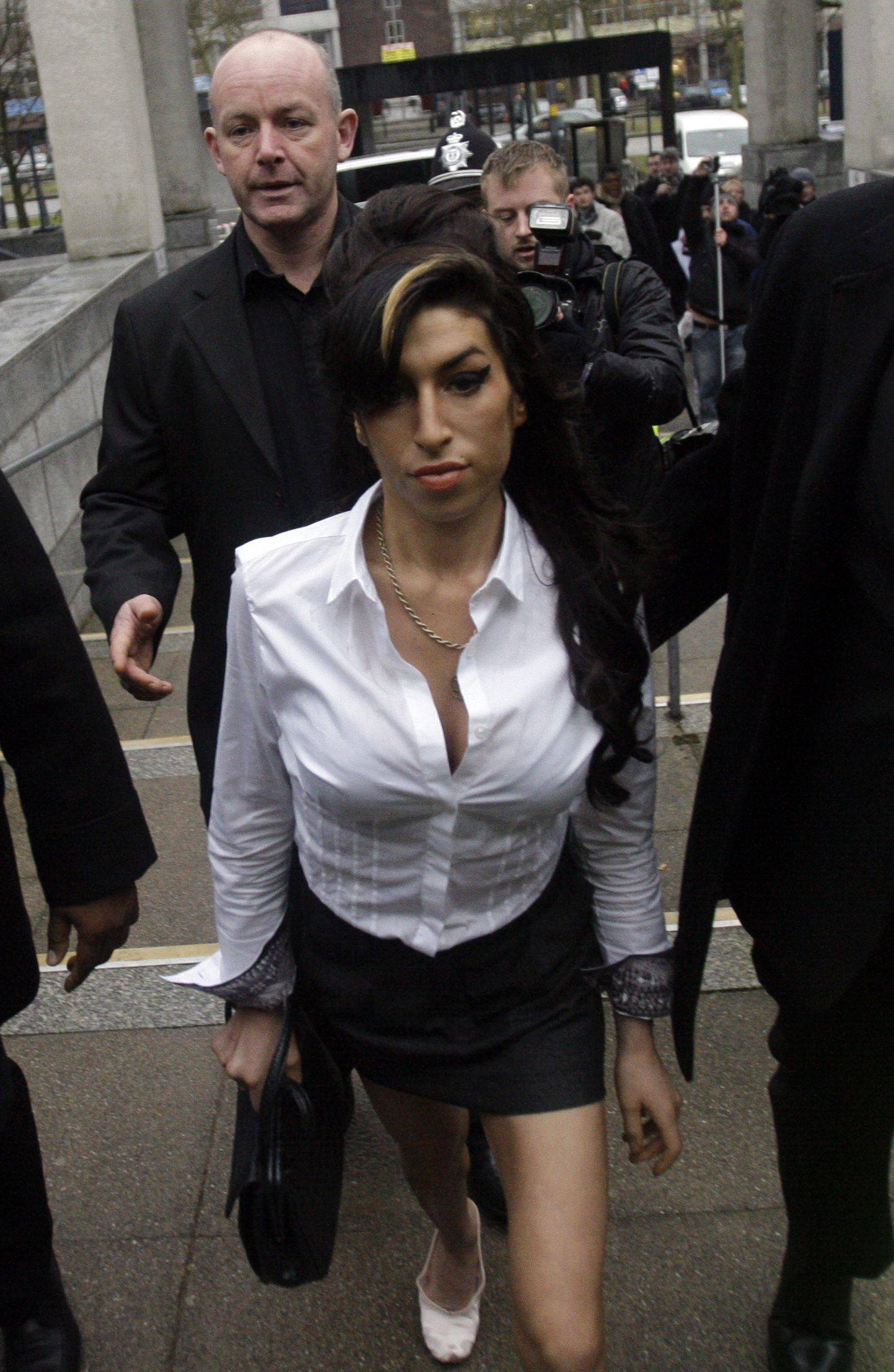 "British singer Amy Winehouse arrives at Magistrates Court in Milton Keynes, England, Wednesday, Jan. 20, 2010. Winehouse pleaded guilty Wednesday to assaulting a theater manager at a family Christmas show. The 26-year-old admitted charges of disorder and common assault during a Dec. 19 performance of the pantomime, or variety show, ""Cinderella."" (AP Photo/Matt Dunham)"