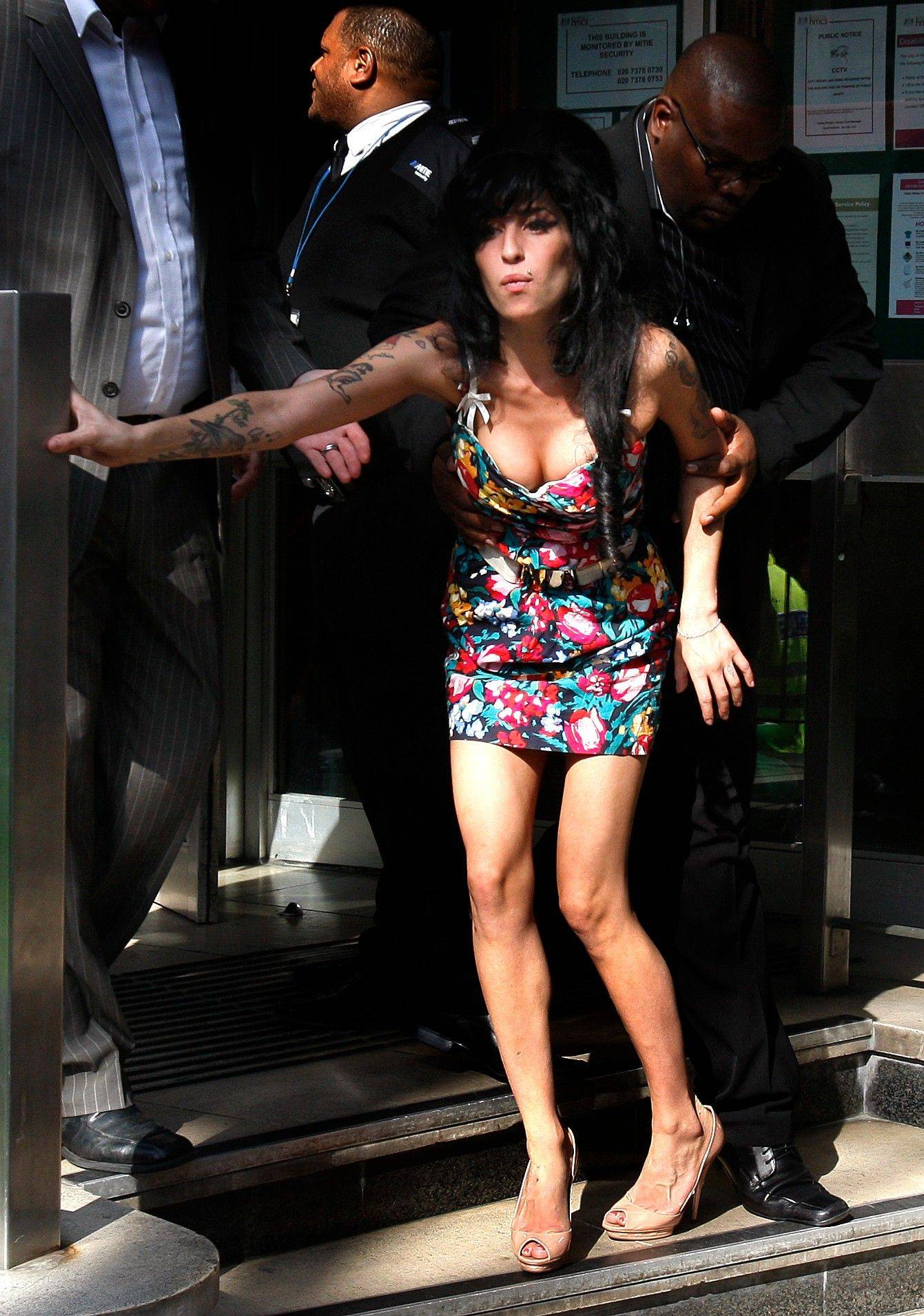 Amy Winehouse is assisted as she leaves Westminster Magistrates Court in London, where she pleaded not guilty to a charge of common assault, over an incident at a charity ball.
