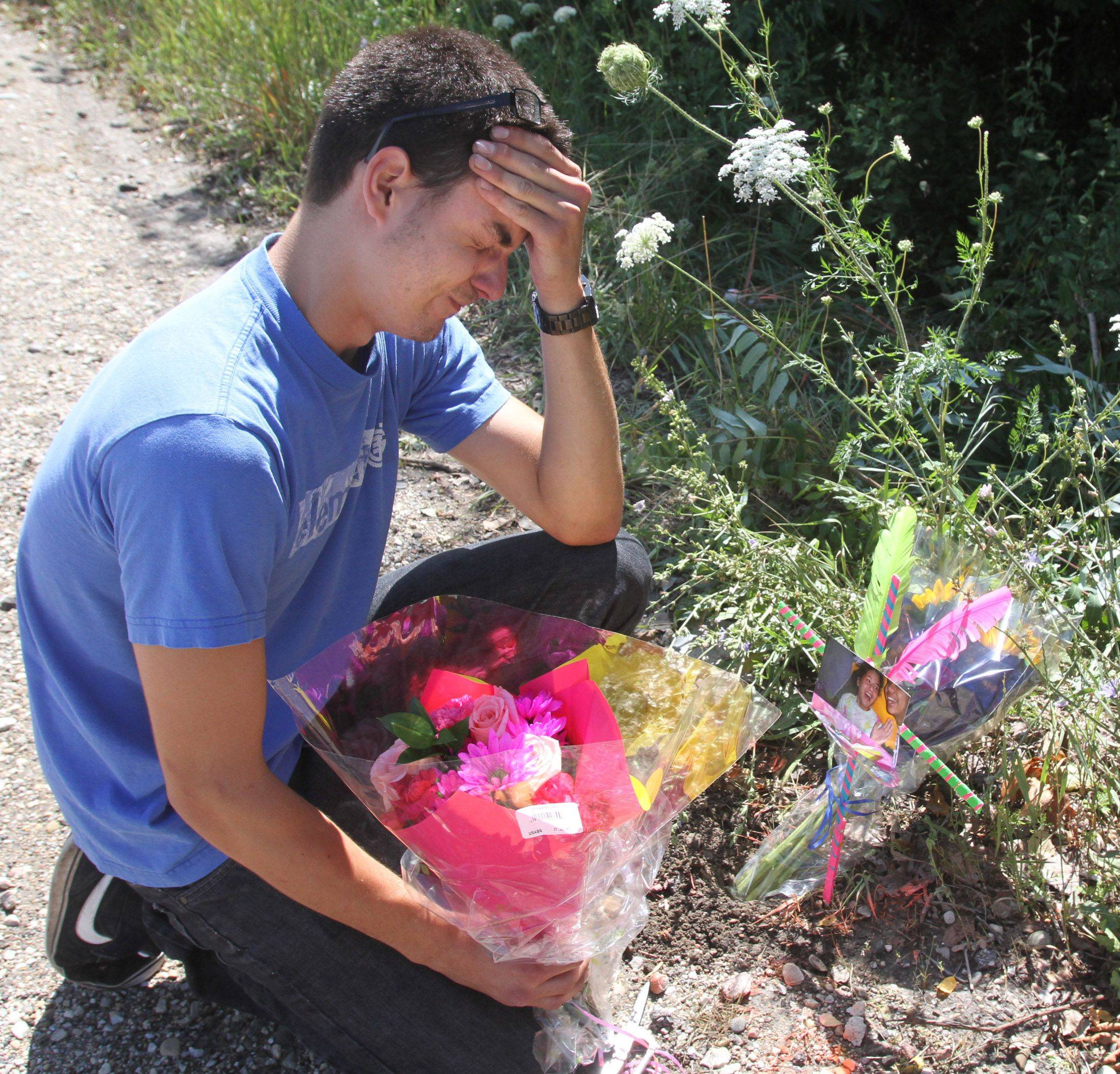 David Borcean places flowers at the scene where a Lake Zurich teen was killed after a hit-and-run in Lake Zurich on Friday night. Two other teens were injured.
