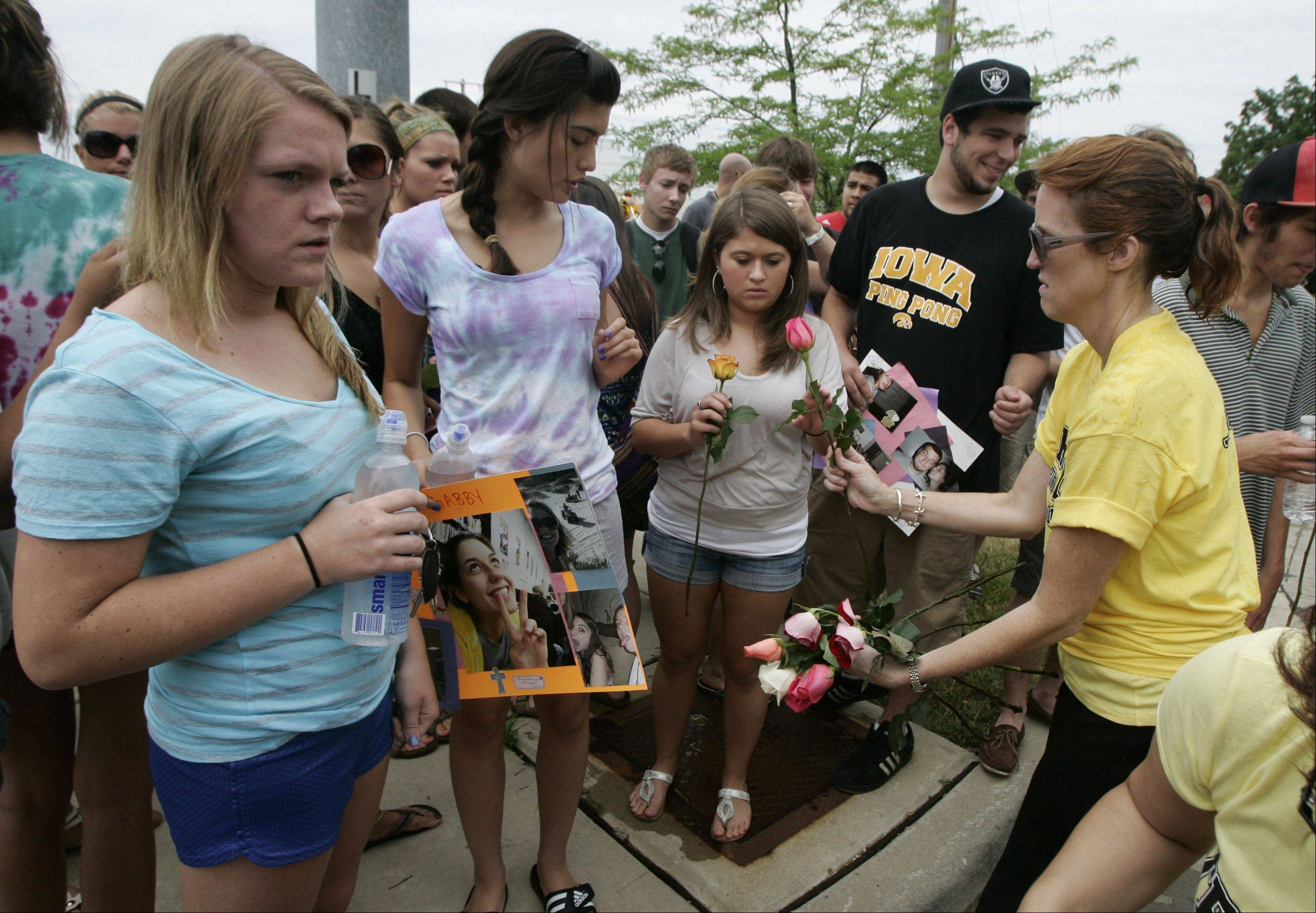 Annie Sadowski, right, of Trilogy Dance in Lake Zurich, hands out flowers to friends and family of hit-and-run victim Gabriella Drozdz during the Lake Zurich Alpine Festival parade Sunday. Drozdz, of Lake Zurich, was killed by someone driving an SUV Friday night as she and two other friends were walking along Church Street on their way to Alpine Fest.