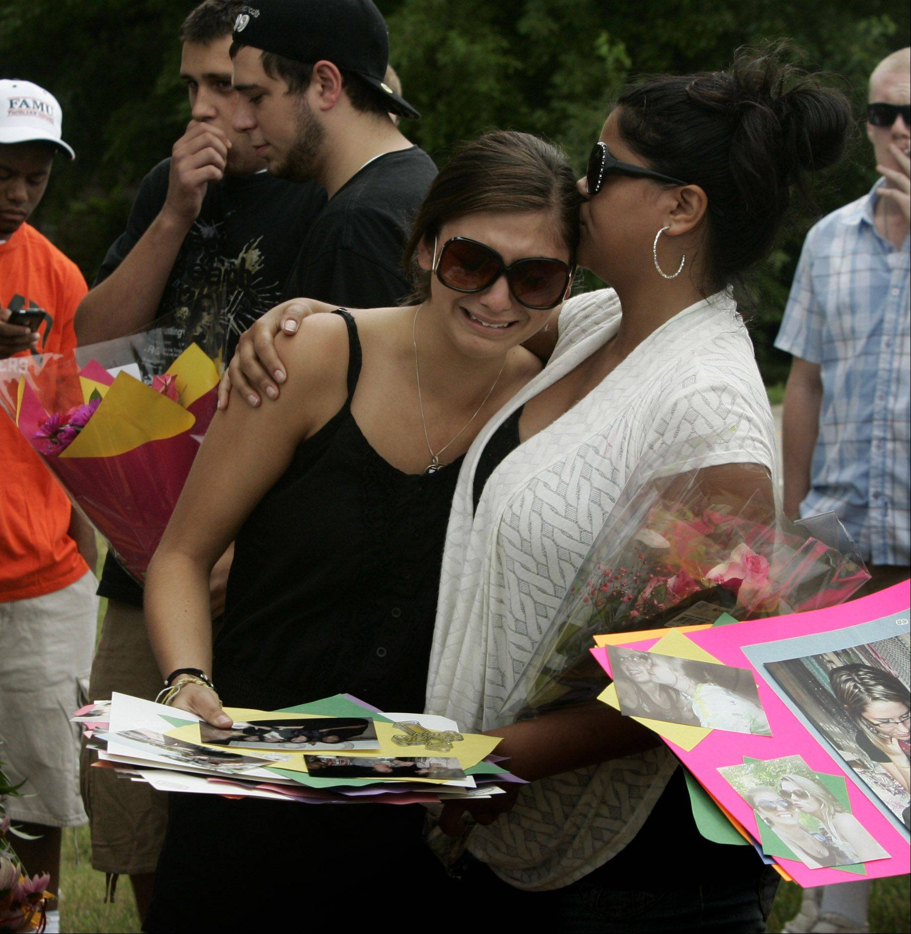 Dana Lebron, right, comforts Kara Sprinkle as friends and family gather and march in the Lake Zurich Alpine Festival parade Sunday in memory of hit-and-run victim Gabriella Drozdz. Drozdz, of Lake Zurich, was killed by someone driving an SUV Friday night as she and two other friends were walking along Church Street on their way to Alpine Fest community festival.