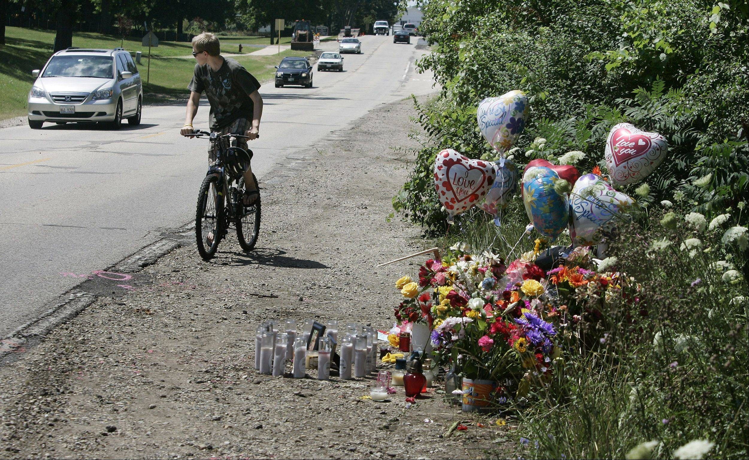 A bicyclist watches out for traffic as he rides on the shoulder near a memorial set up along Church Street in Lake Zurich for hit-and-run victim Gabriella Drozdz. The Lake Zurich teenager was killed and two friends were injured when they were hit by an SUV Friday night as they walked to Alpine Fest.
