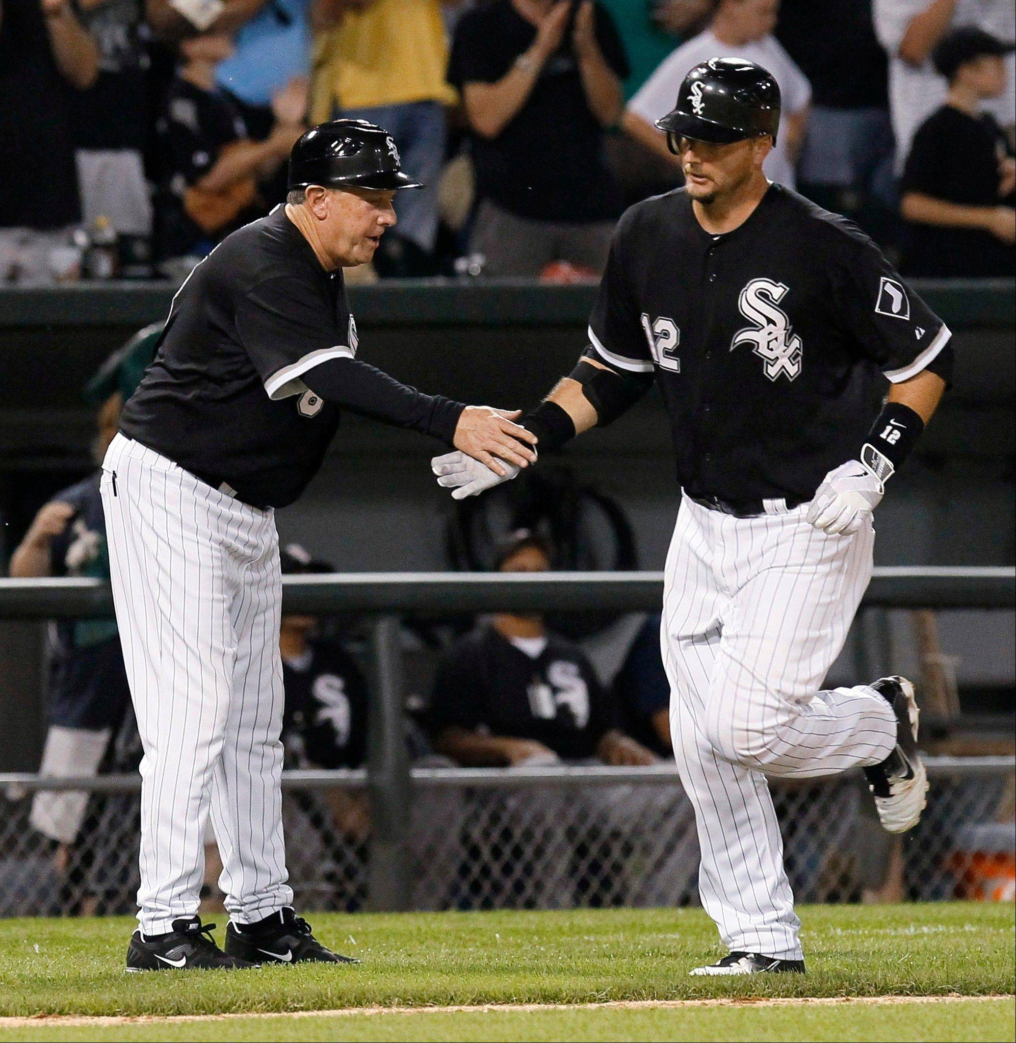 White Sox third base coach Jeff Cox, left, greets A.J. Pierzynski after his home run off Detroit Tigers relief pitcher Chance Ruffin during Monday's sixth inning at U.S. Cellular Field.