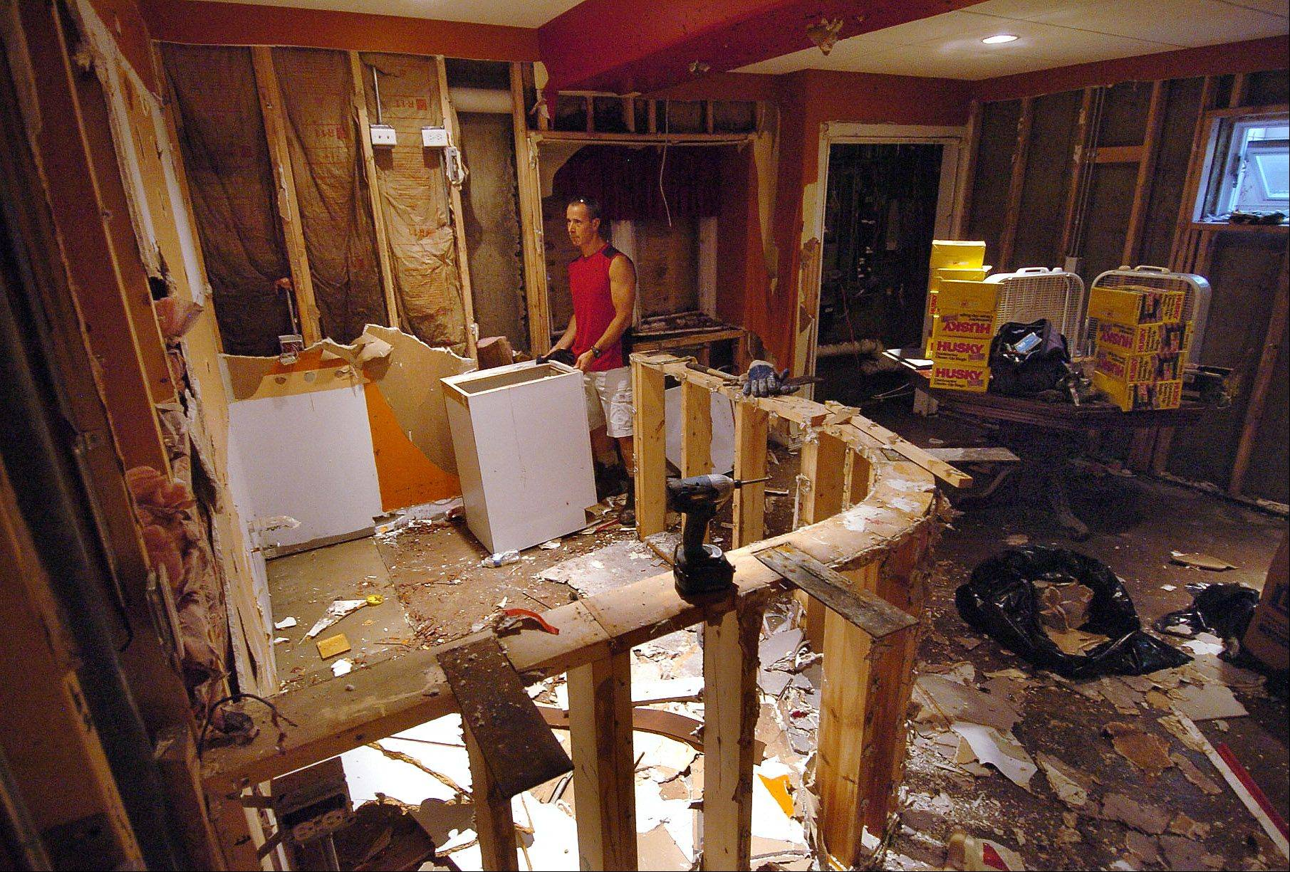 Mike Donner of Arlington Heights clears out some of the flood damage to his basement.