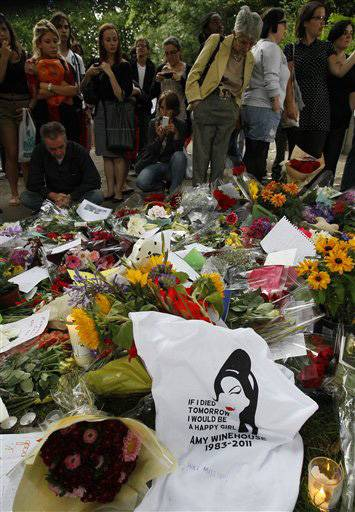 Fans gather around flowers and tributes near the home of British singer Amy Winehouse in London, Monday.