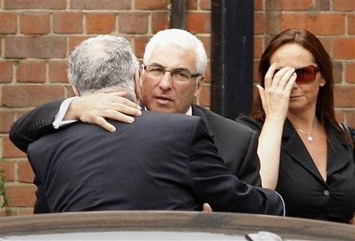 Mitch Winehouse, center, the father of British singer Amy Winehouse, is consoled as he arrives at Golders Green Crematorium.